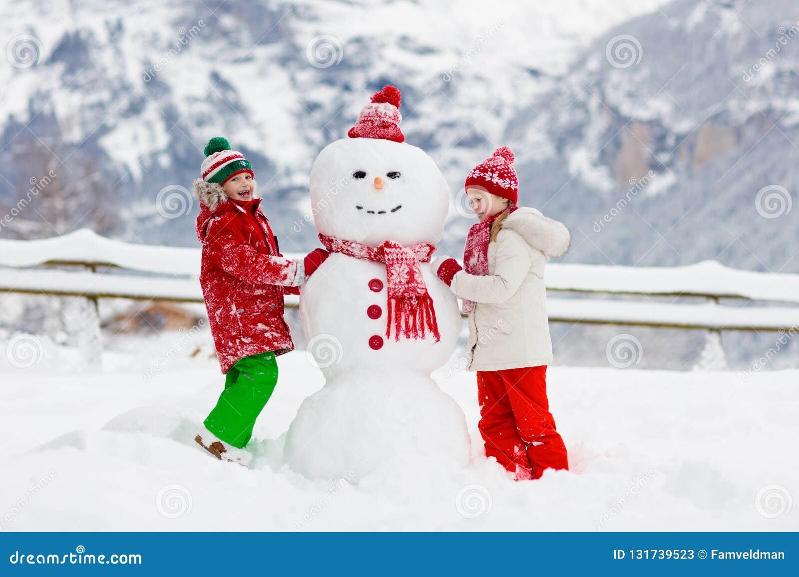 Barnbyggnadssnögubbe Ungar bygger snömannen Pojke och flicka som utomhus spelar på snöig vinterdag