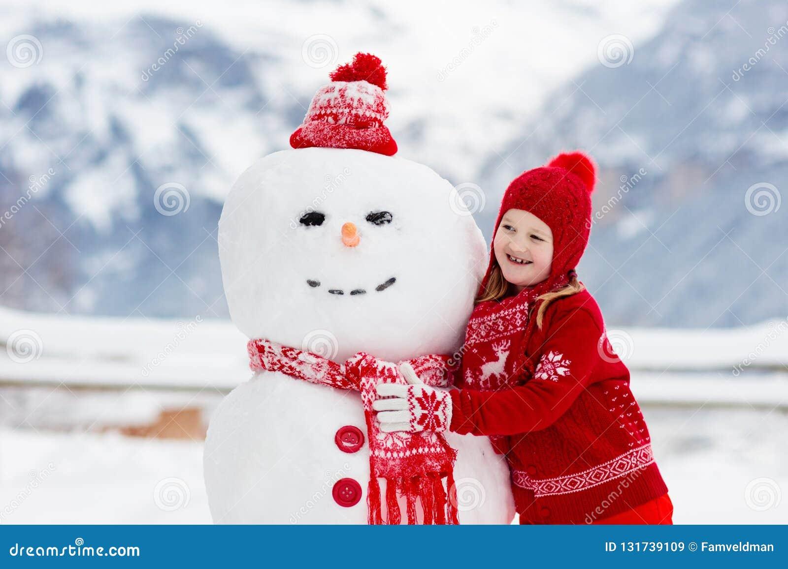 Barnbyggnadssnögubbe Ungar bygger snömannen Pojke och flicka som utomhus spelar på snöig vinterdag Utomhus- familjgyckel på jul