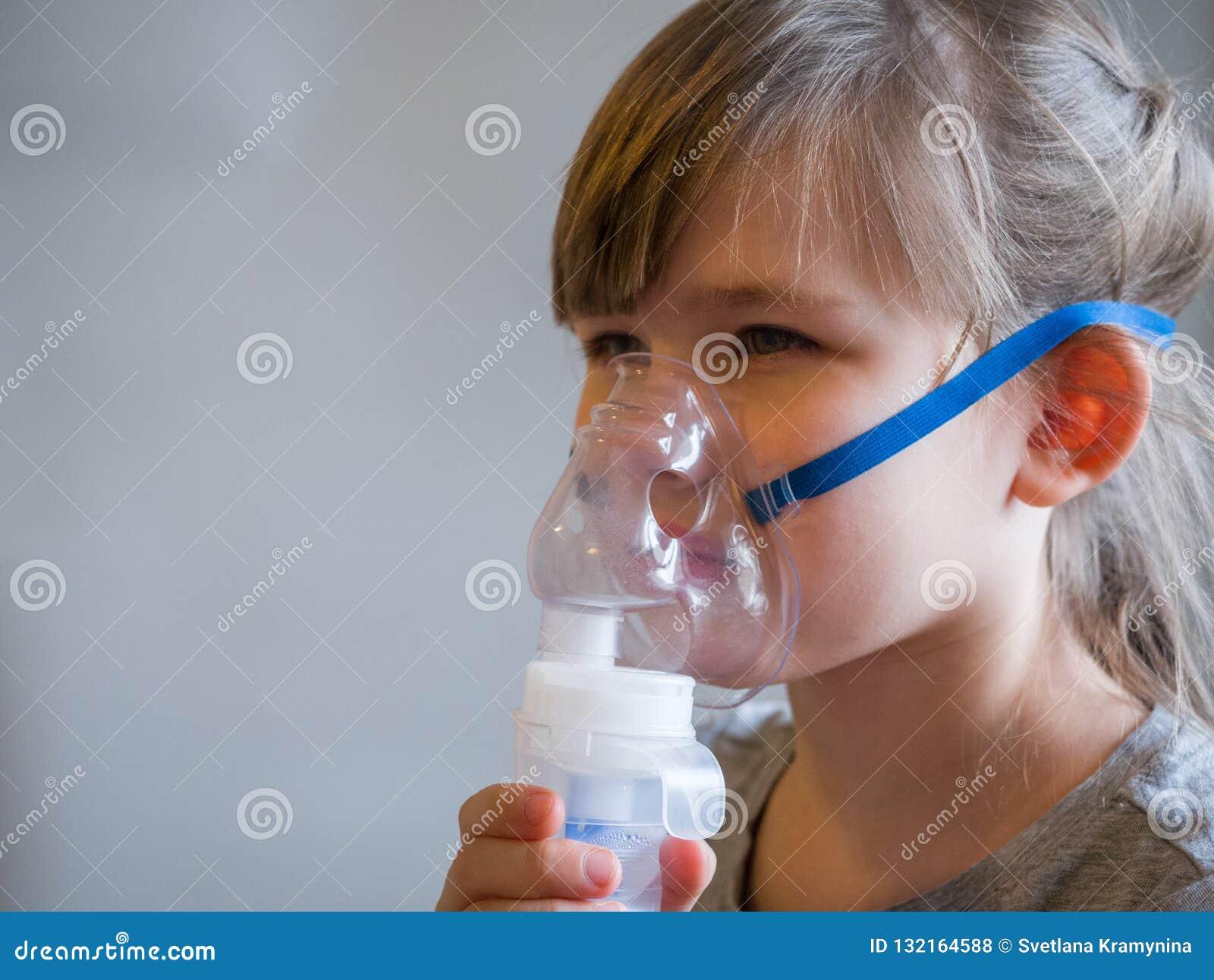 Barndanandeinandning med maskeringen på hans framsida Astmaproblembegrepp