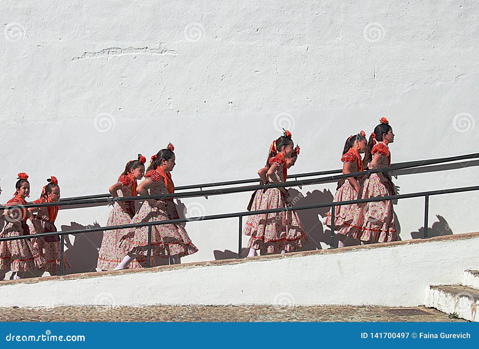 Barndansare som går till etappen under den corpusChristi Procession festivalen i Ronda
