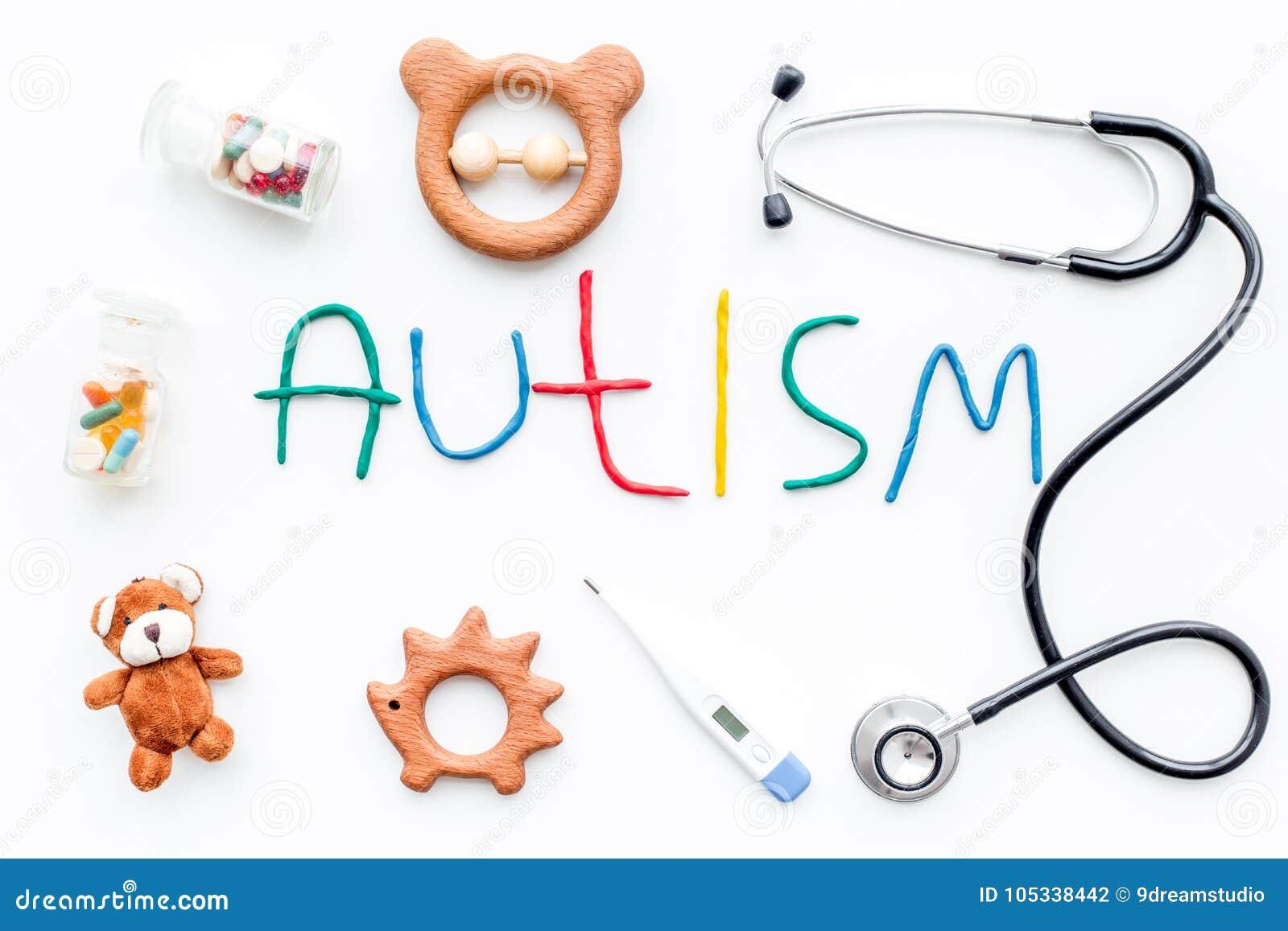 Barndomsjukdomar Uttrycka autism nära stetoscope, preventivpillerar, leksaker på bästa sikt för vit bakgrund
