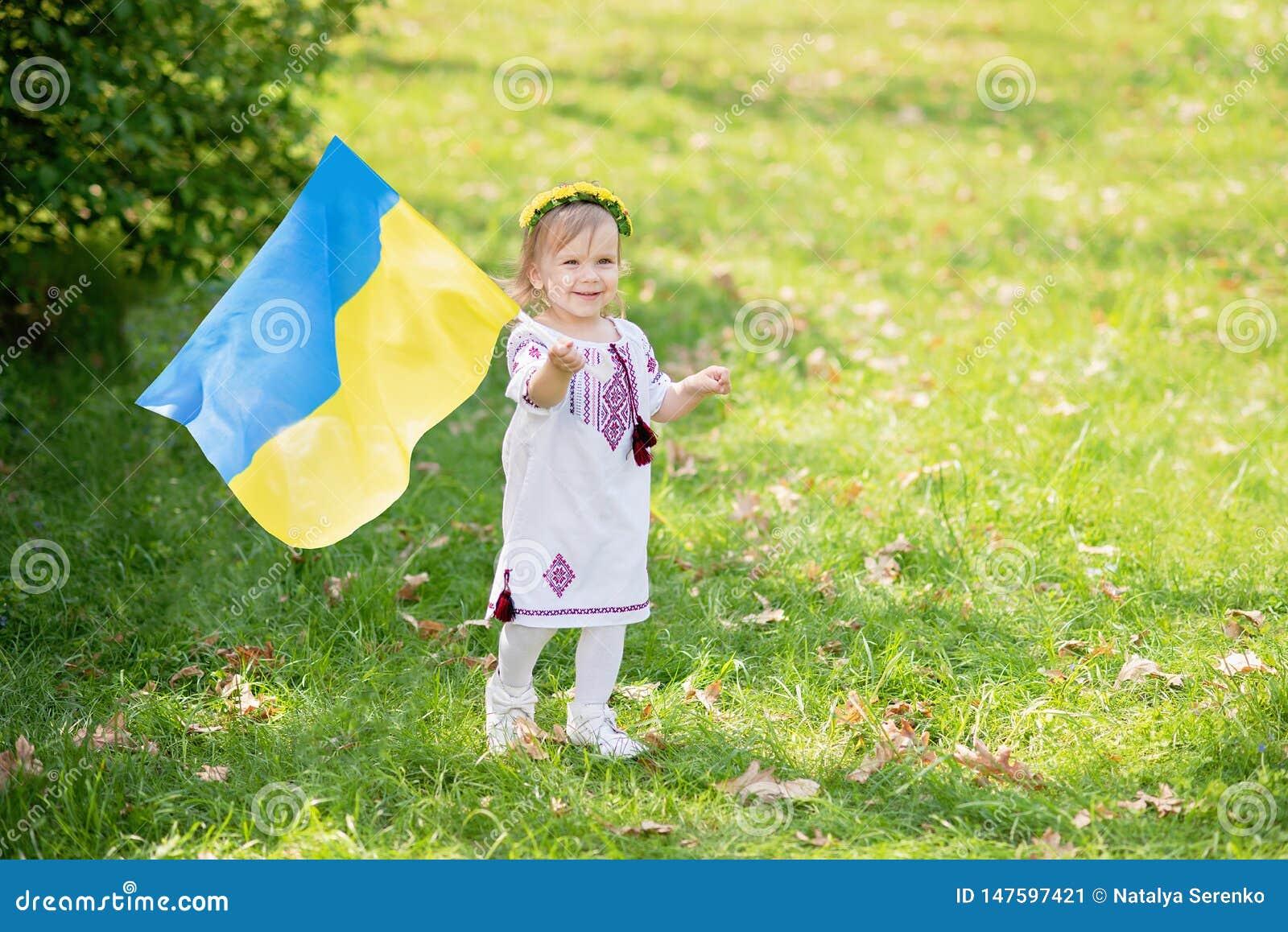 Barnet b?r att fladdra den bl?a och gula flaggan av Ukraina i f?lt Sj?lvst?ndighetsdagen f?r Ukraina ` s f?r dagfyrverkerier f?r
