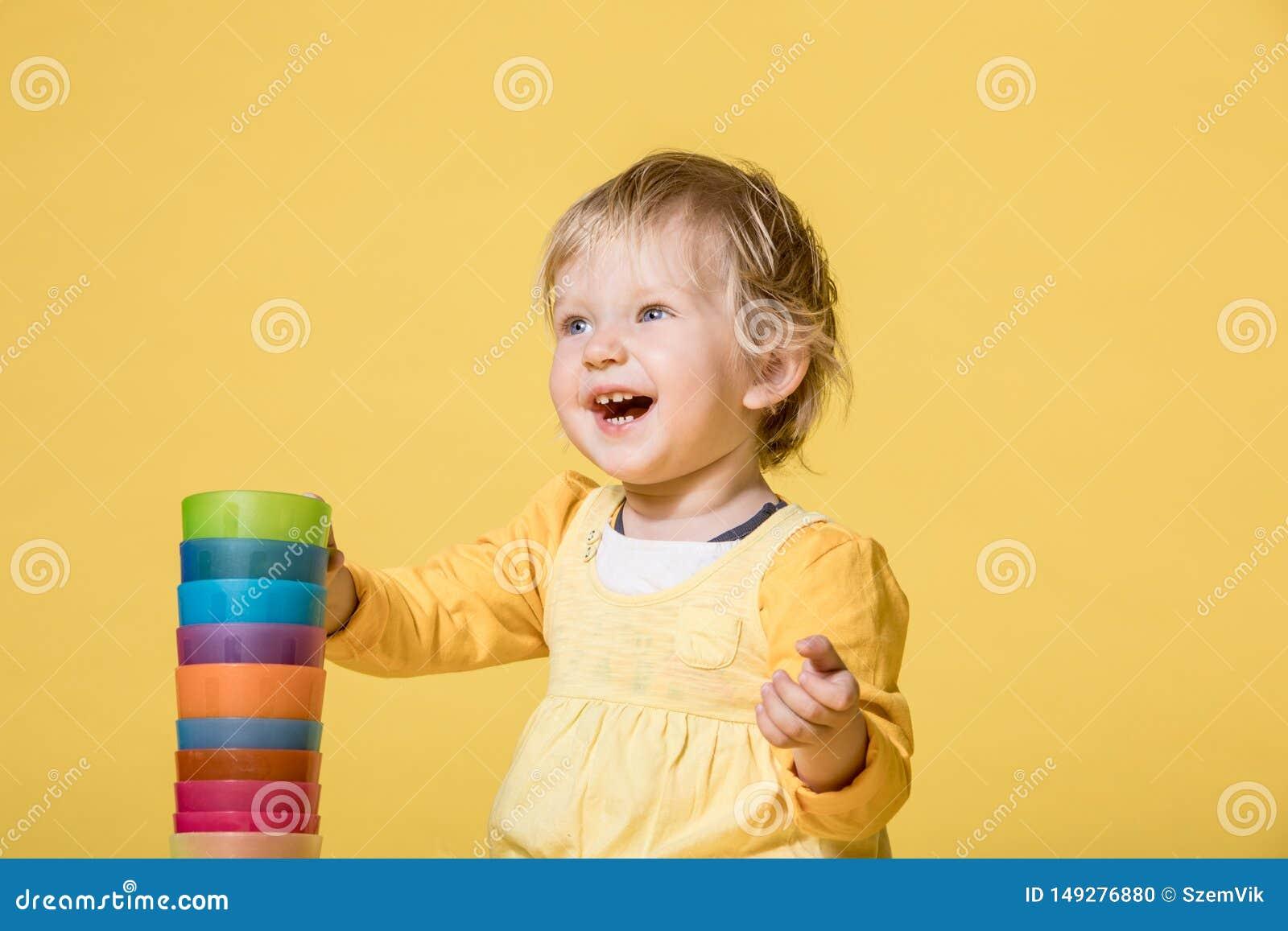 Barnet behandla som ett barn flickan i gul kl?nning p? gul bakgrund
