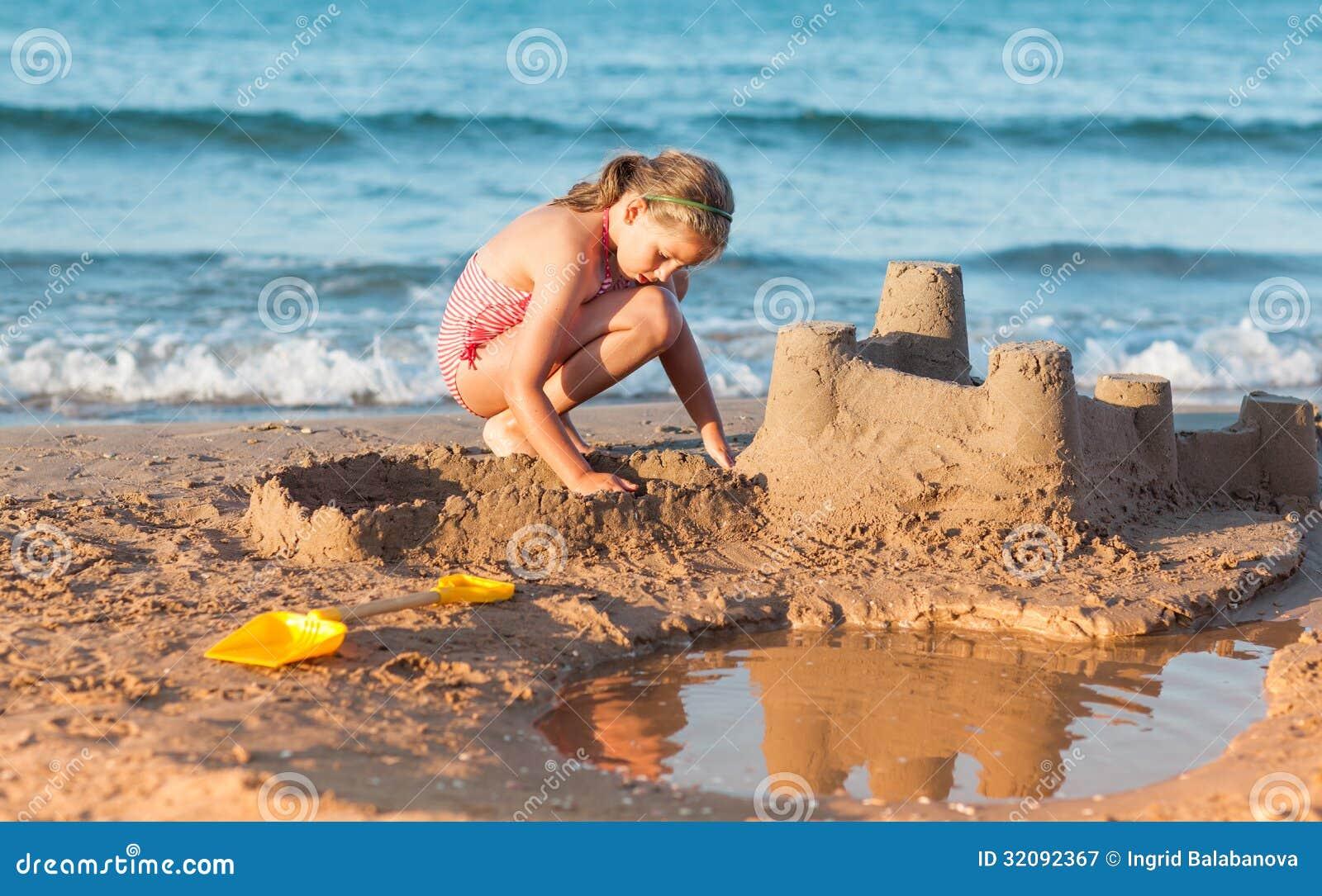 Barnet bygger sandslotten på stranden