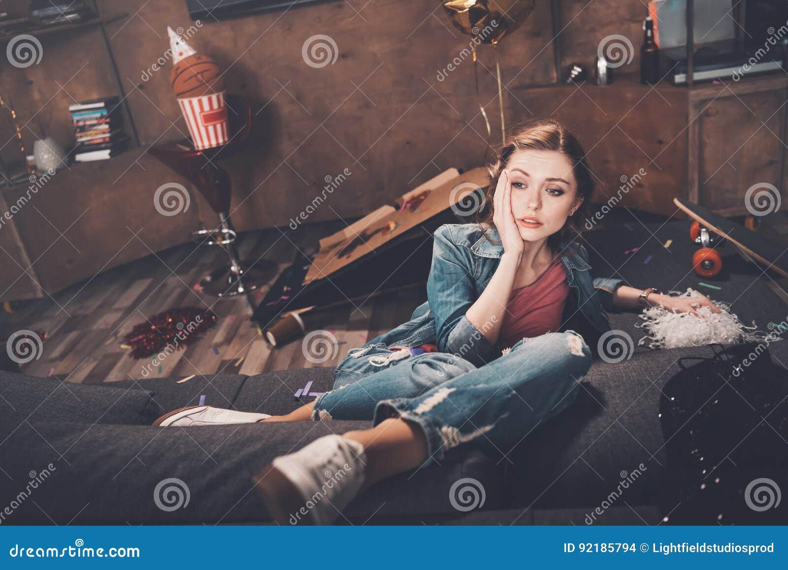 Barnet förargar kvinnan med bakrussammanträde på soffan i smutsigt rum