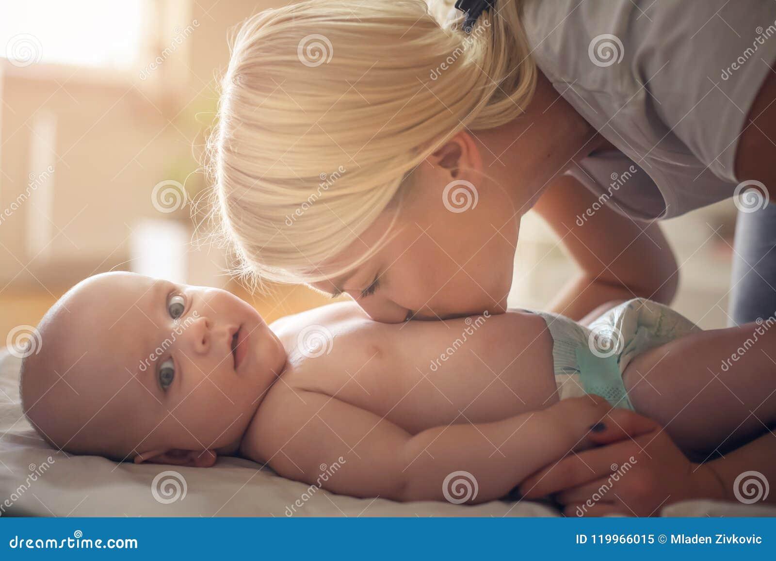 Barnet fostrar att kyssa hennes litet behandla som ett barn i blöjor close upp