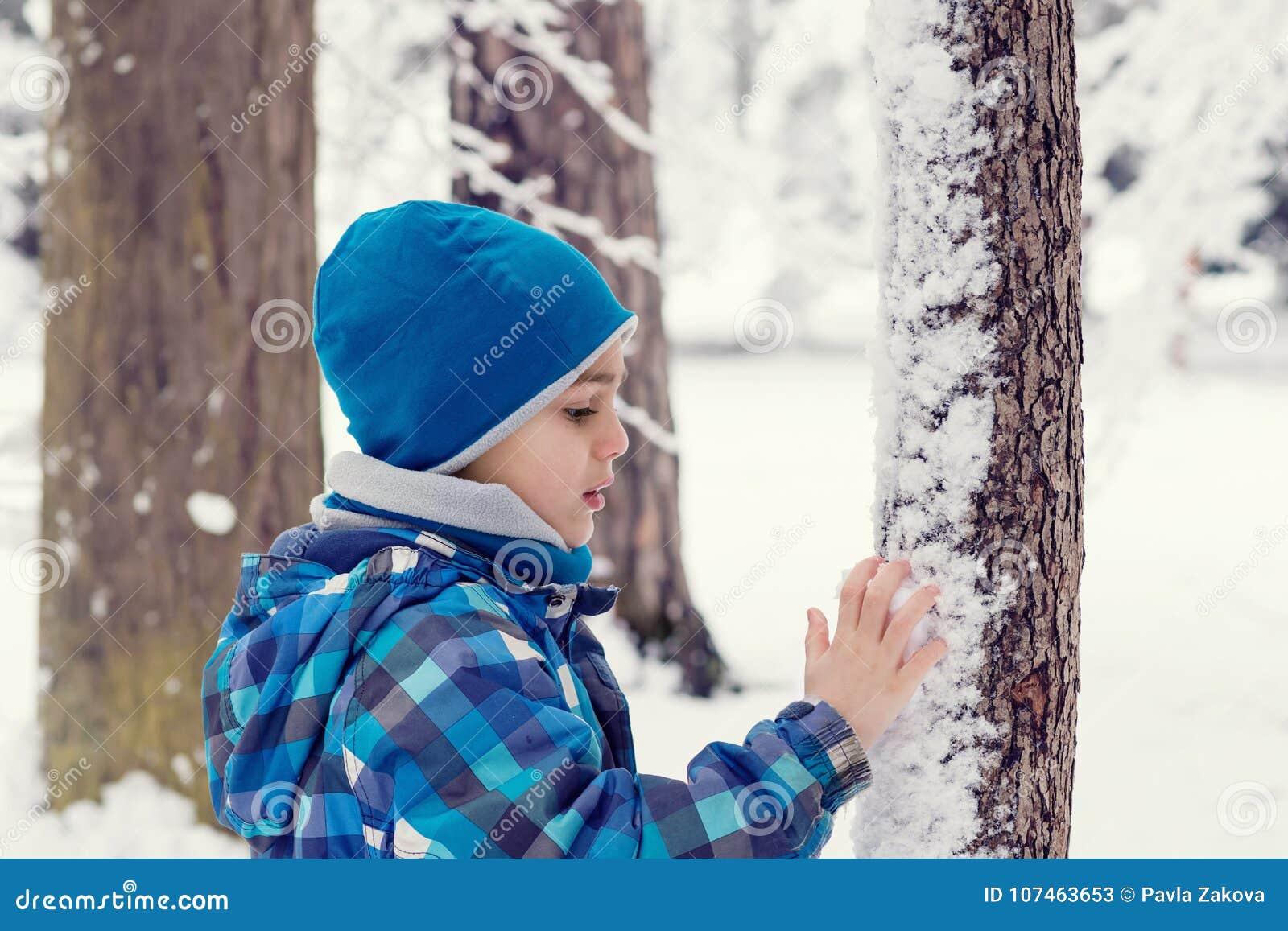 Barnet i en vinter parkerar eller skogen
