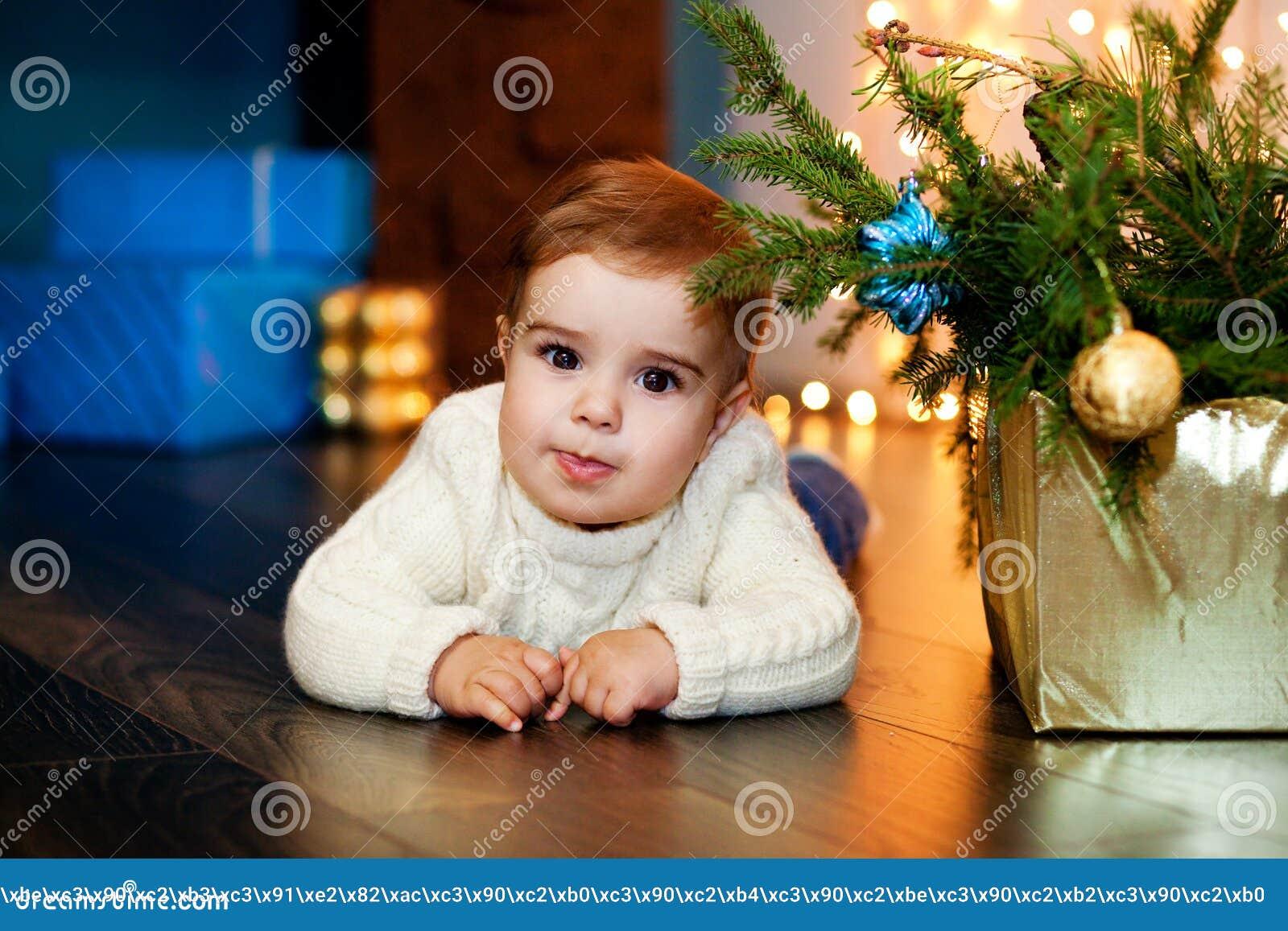 Barnet i en vit tröjalögn bredvid asken med gran förgrena sig på bakgrunden av julljus och gåvor