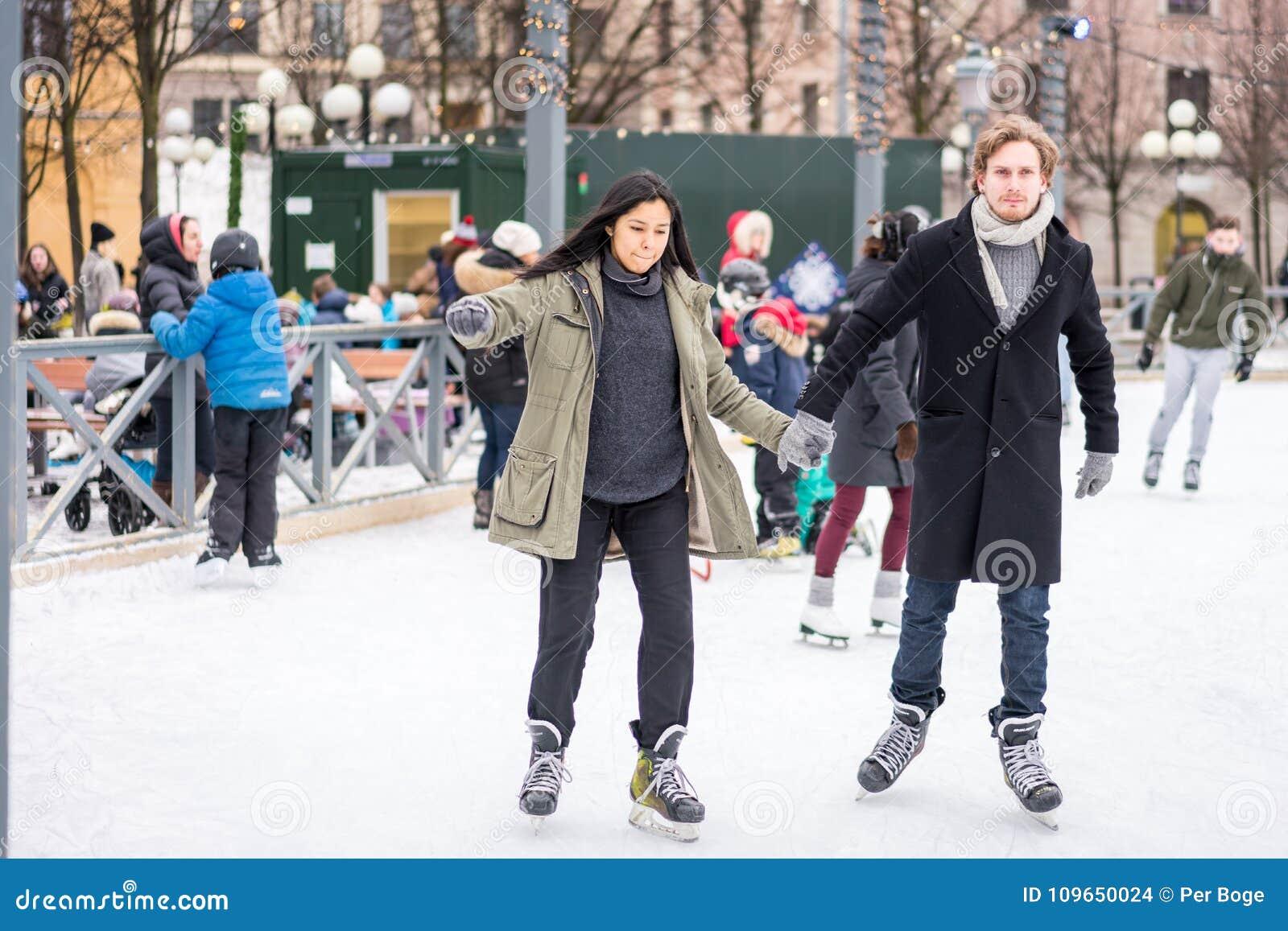 Barnet kopplar ihop att åka skridskor på en offentlig skridskoåkningisbana utomhus i staden