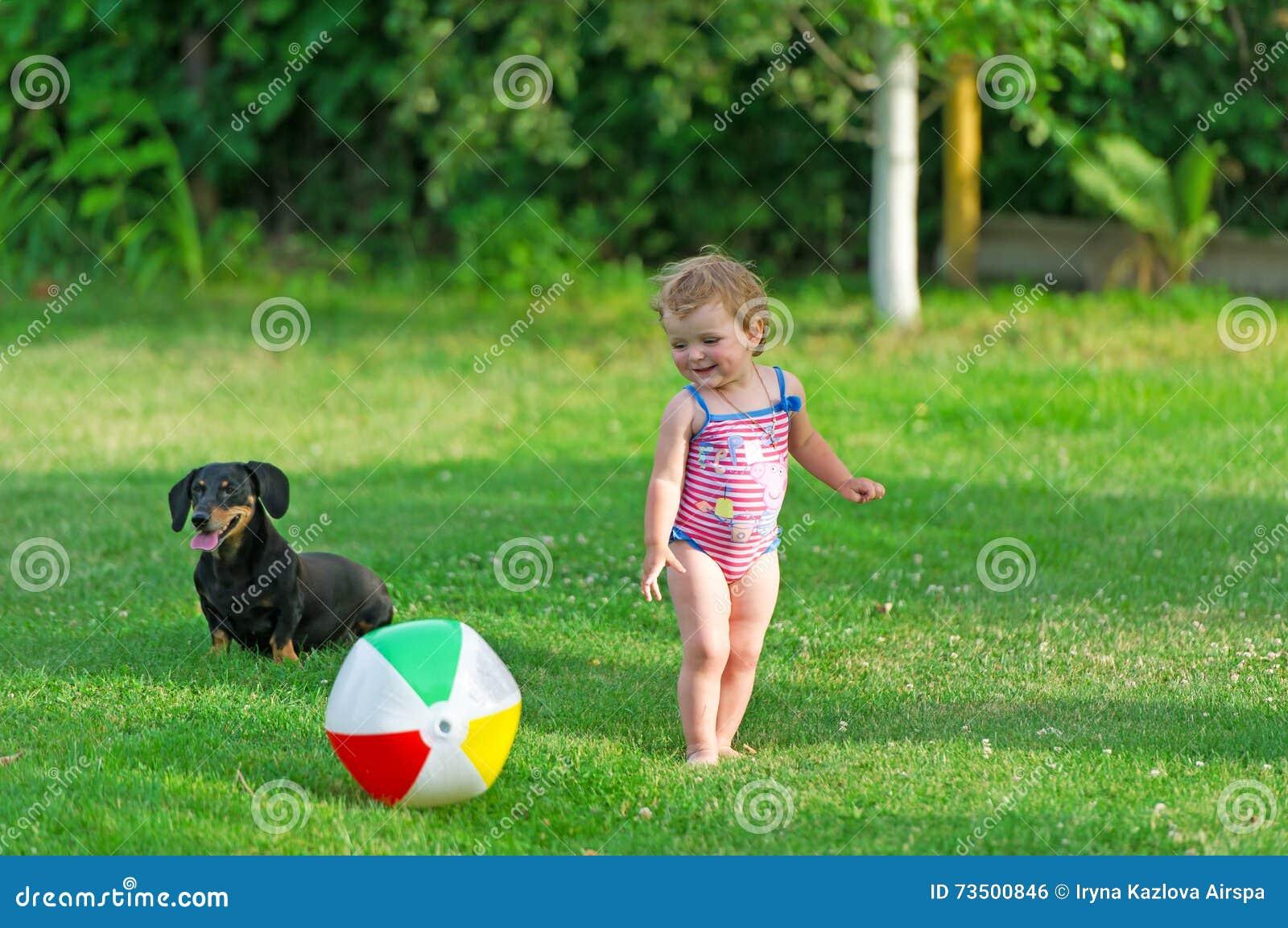 Barnet och hunden spelar i ett gräs