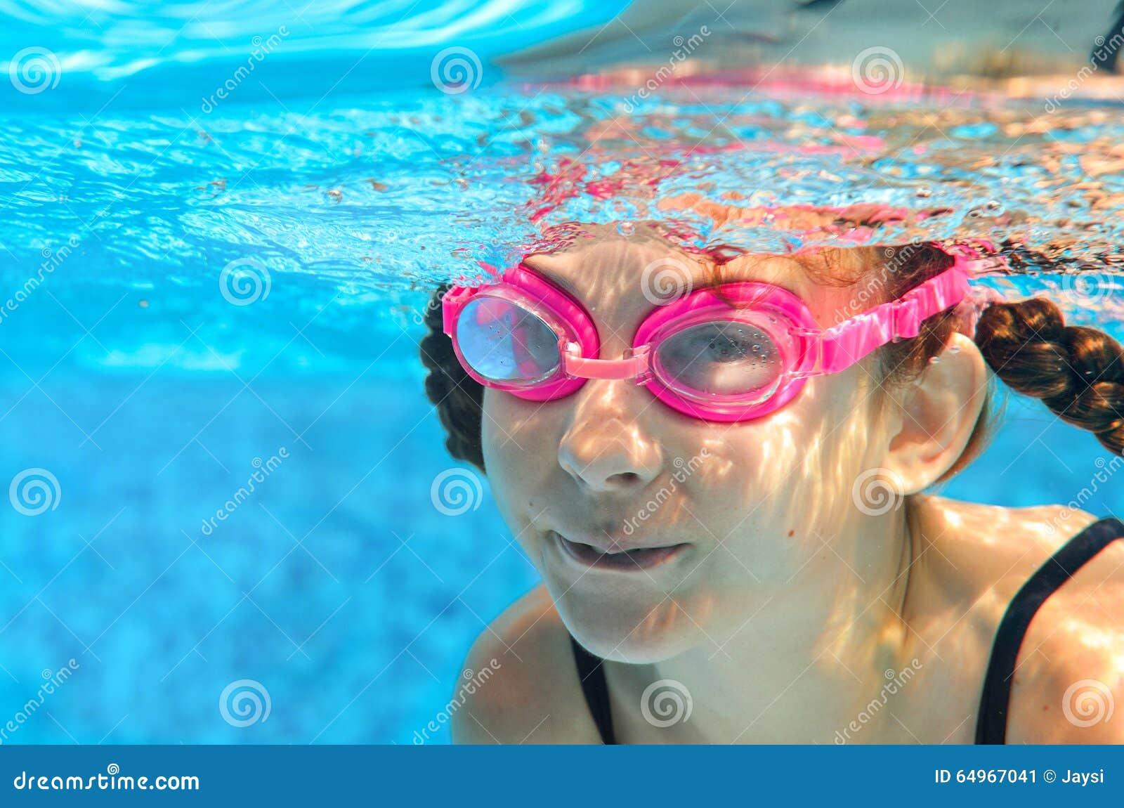 Barnet simmar i den undervattens- pölen, den lyckliga aktiva flickan i skyddsglasögon har gyckel i vatten, ungesport på familjsem