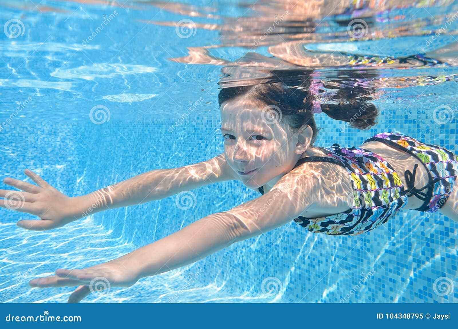 Barnet simmar i den undervattens- pölen, den lyckliga flickan dyker och har gyckel under vatten, ungekondition och sport på famil