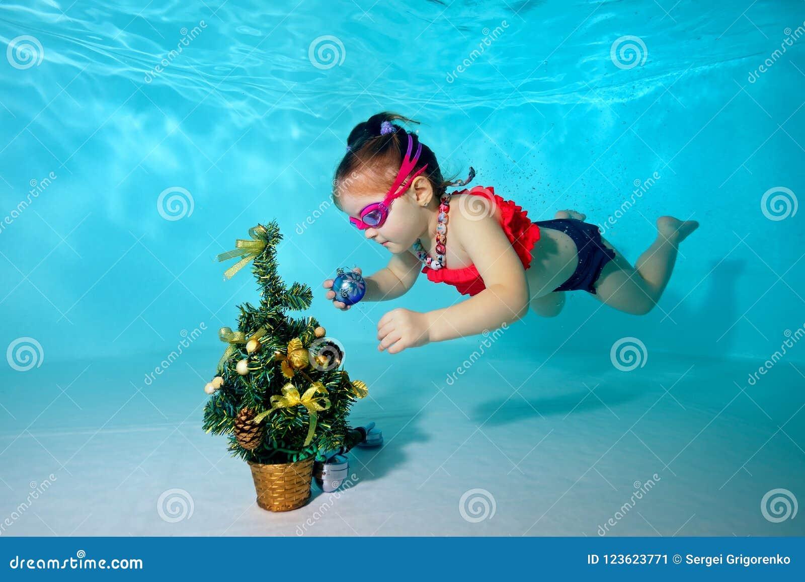 Barnet som är undervattens- i pölen, dekorerar julgranen med julleksaker Stående Skjuta under vatten Horisontalorientat