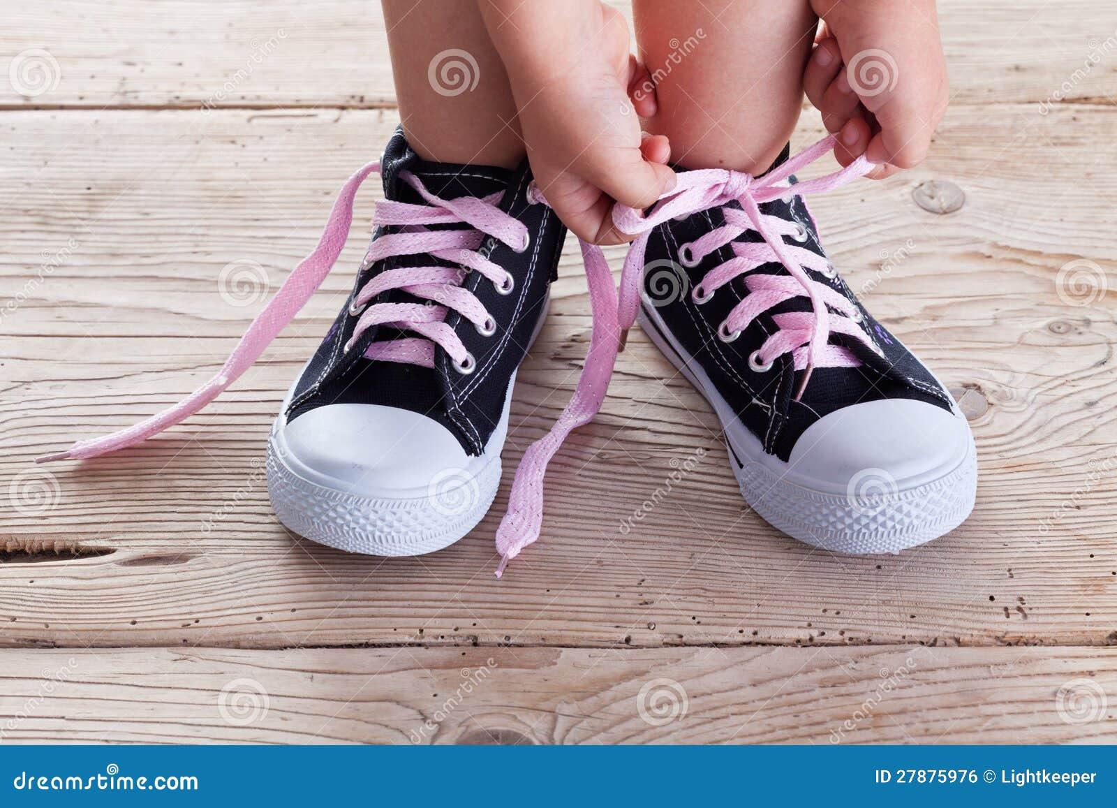 Barnet som händer binder skon, snör åt upp