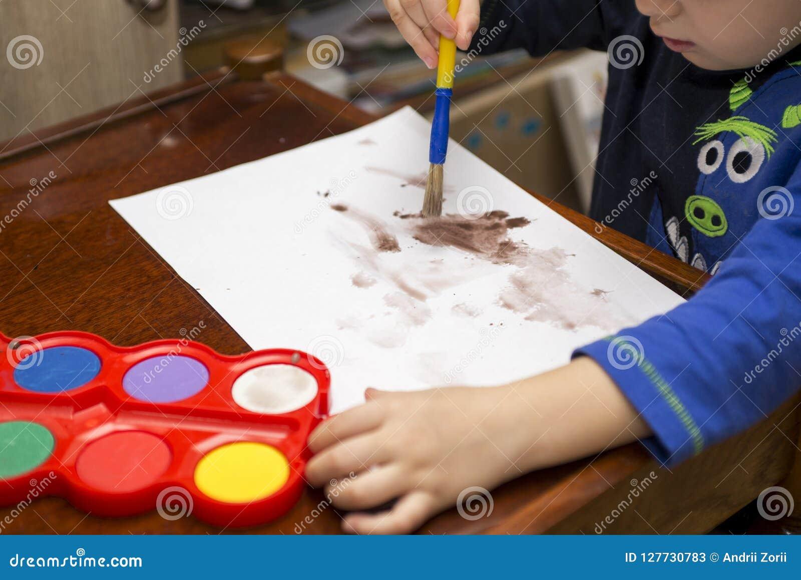 Barnet tecknar målarfärger lego för hand för byggnadsbegreppskreativitet upp väggen