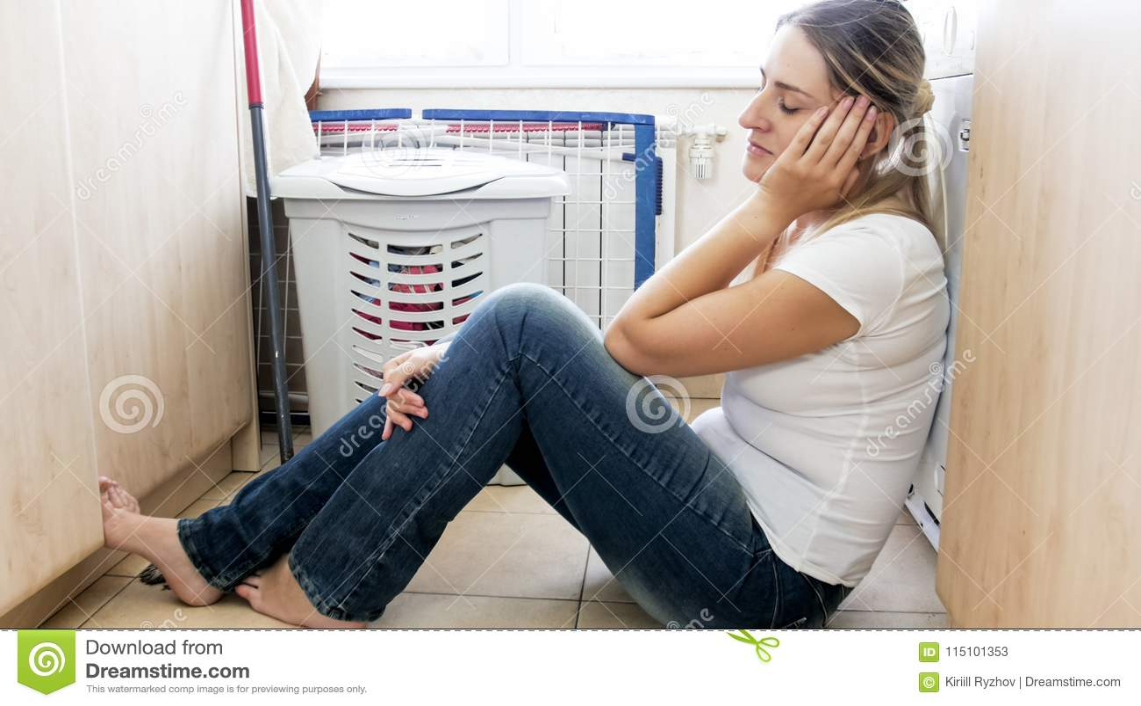 Barnet tröttade kvinnan som sover på golv på tvättstuga, når de har gjort hushållsarbete