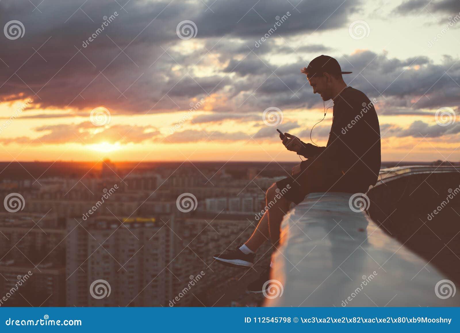 Barnet trotsar mansammanträde på kanten av taket med smartphonen