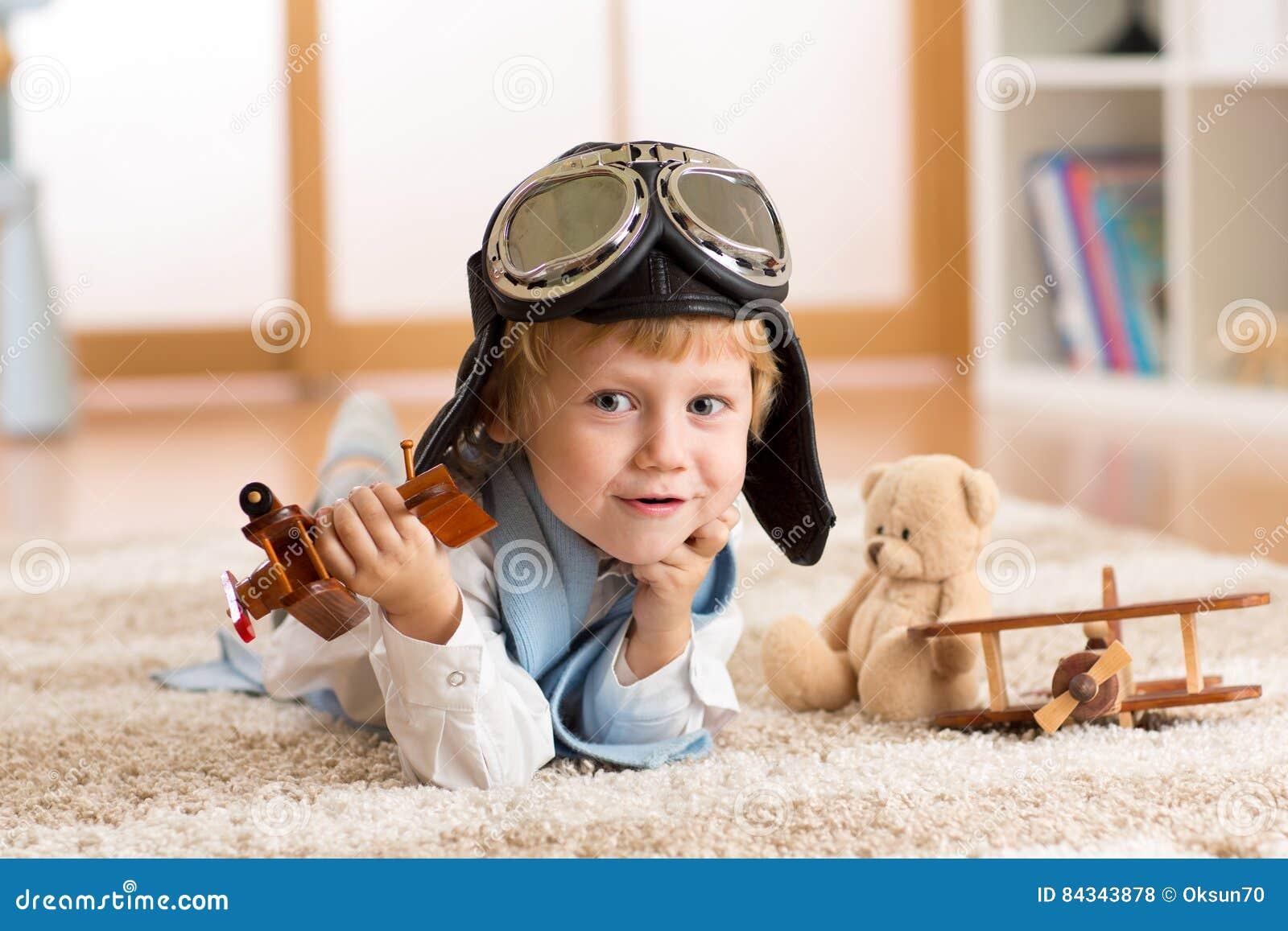 Barnet weared pilot- eller flygarelekar med ett leksakflygplan hemma i barnkammarerum Begrepp av drömmar och resor