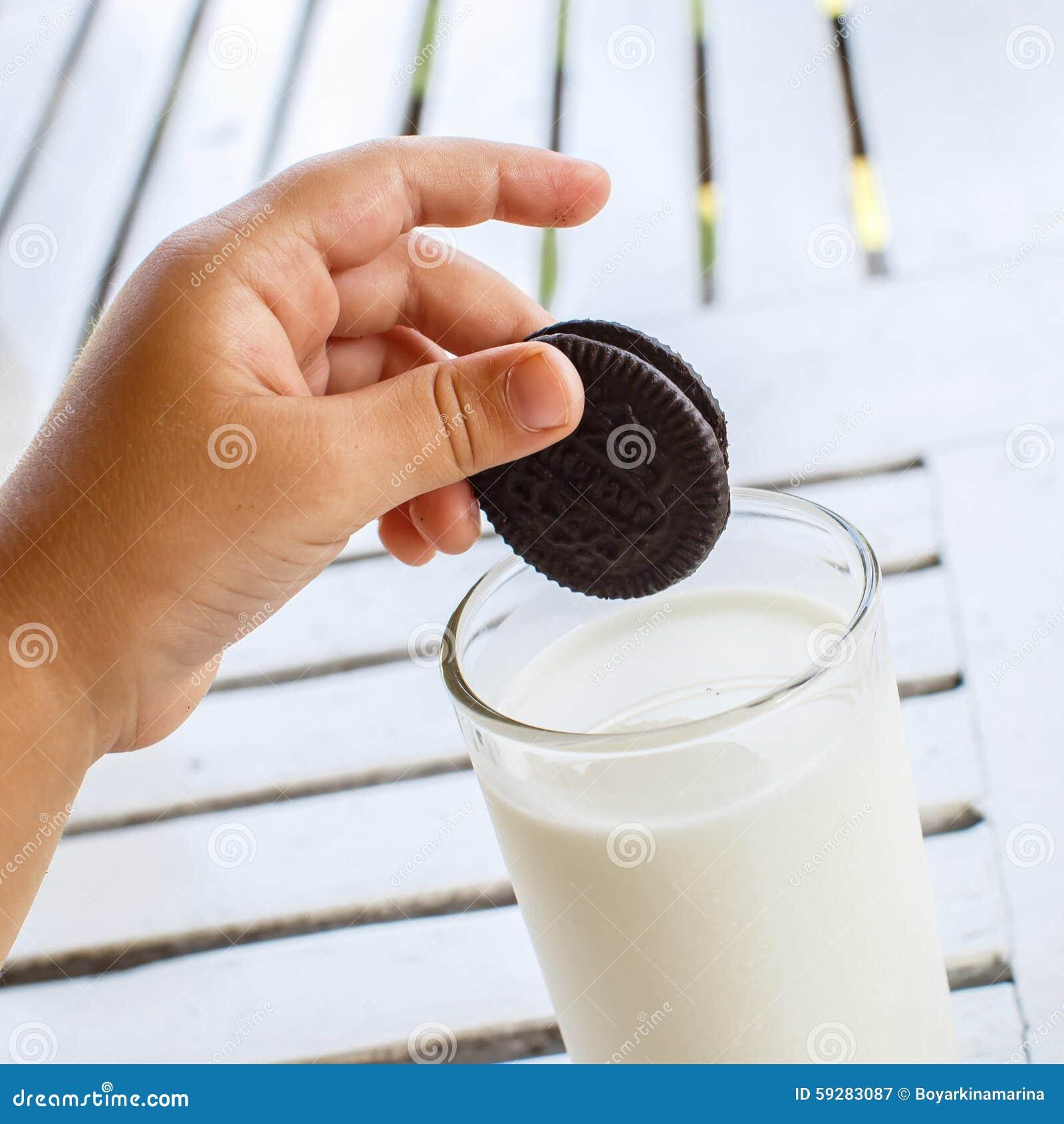 Barnets hand med Oreo kakor fördjupa för att mjölka