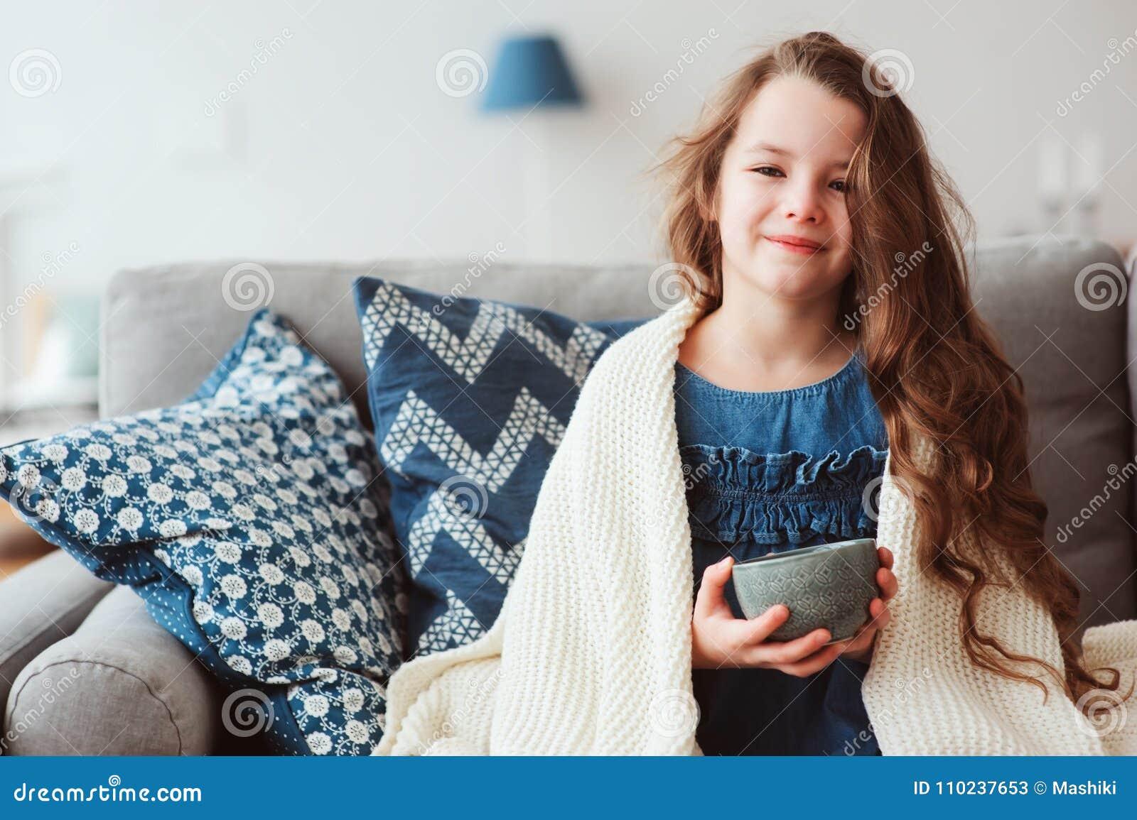 Barnflicka som dricker varmt te för att återställa från influensa