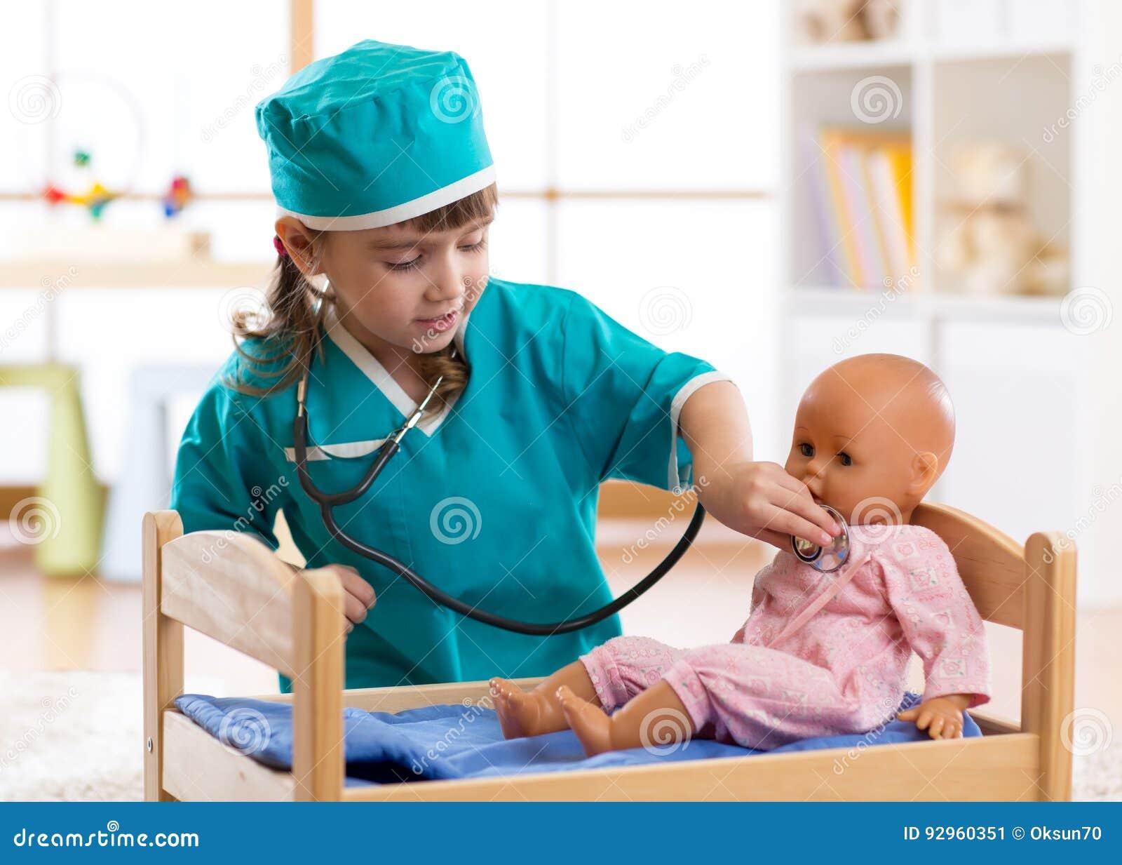 Barnflicka som spelar med dockan i sjukhuset