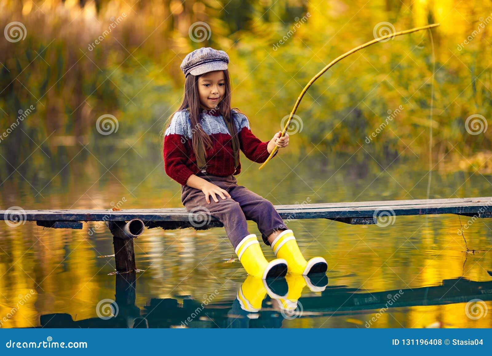Barnflickan sitter på den träfiska bron och fångar fisken i aut
