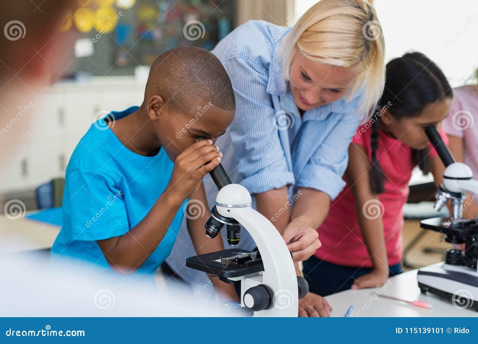 Barnforskare som ser till och med mikroskopet