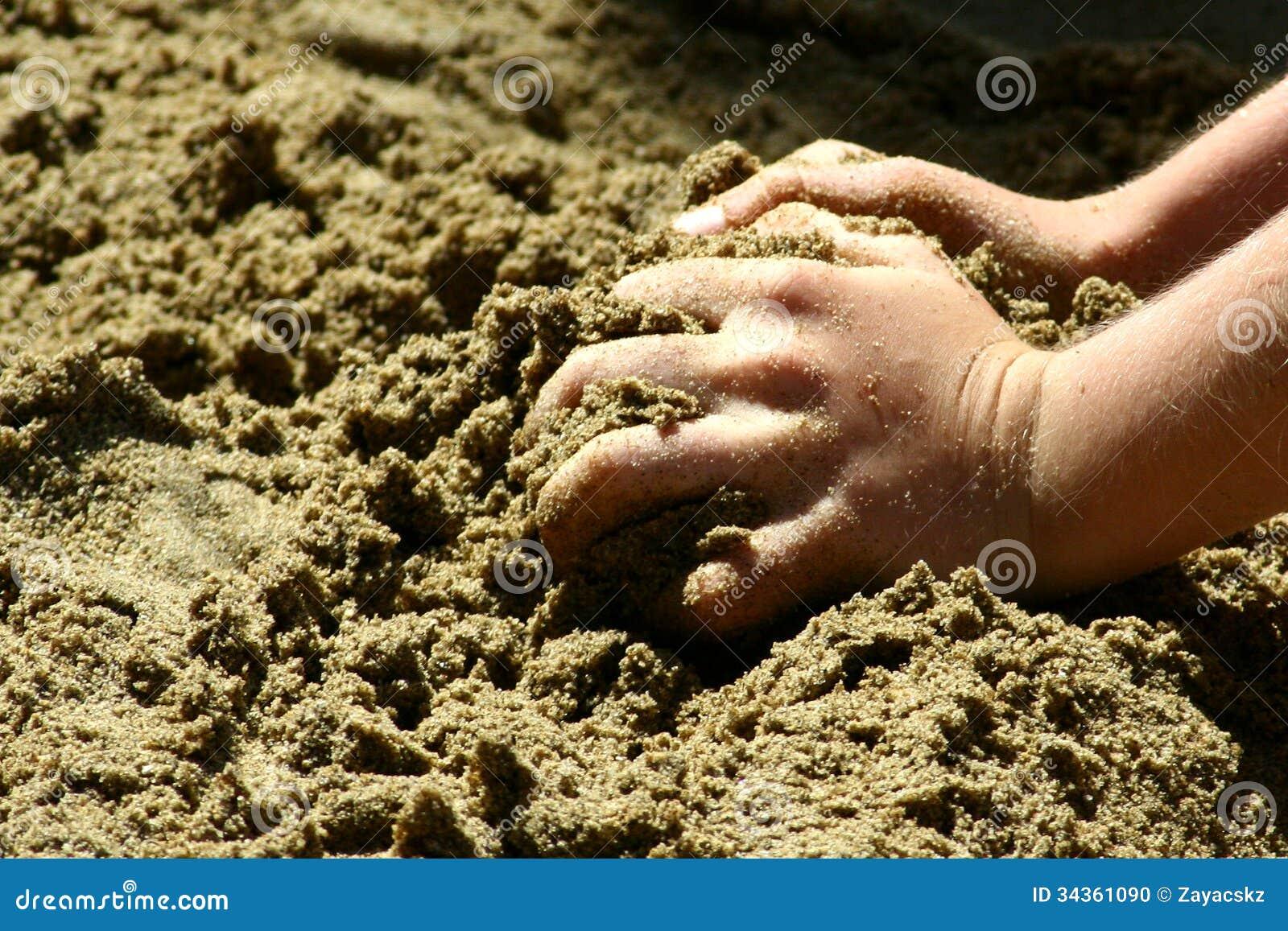 Barnhänder som griper sand på en strand