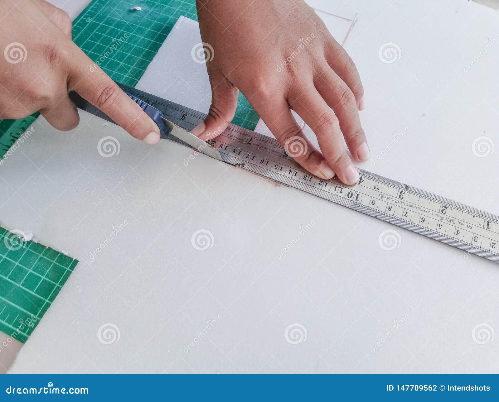 Barnhanden klipper skumpapperet med en skärarekniv