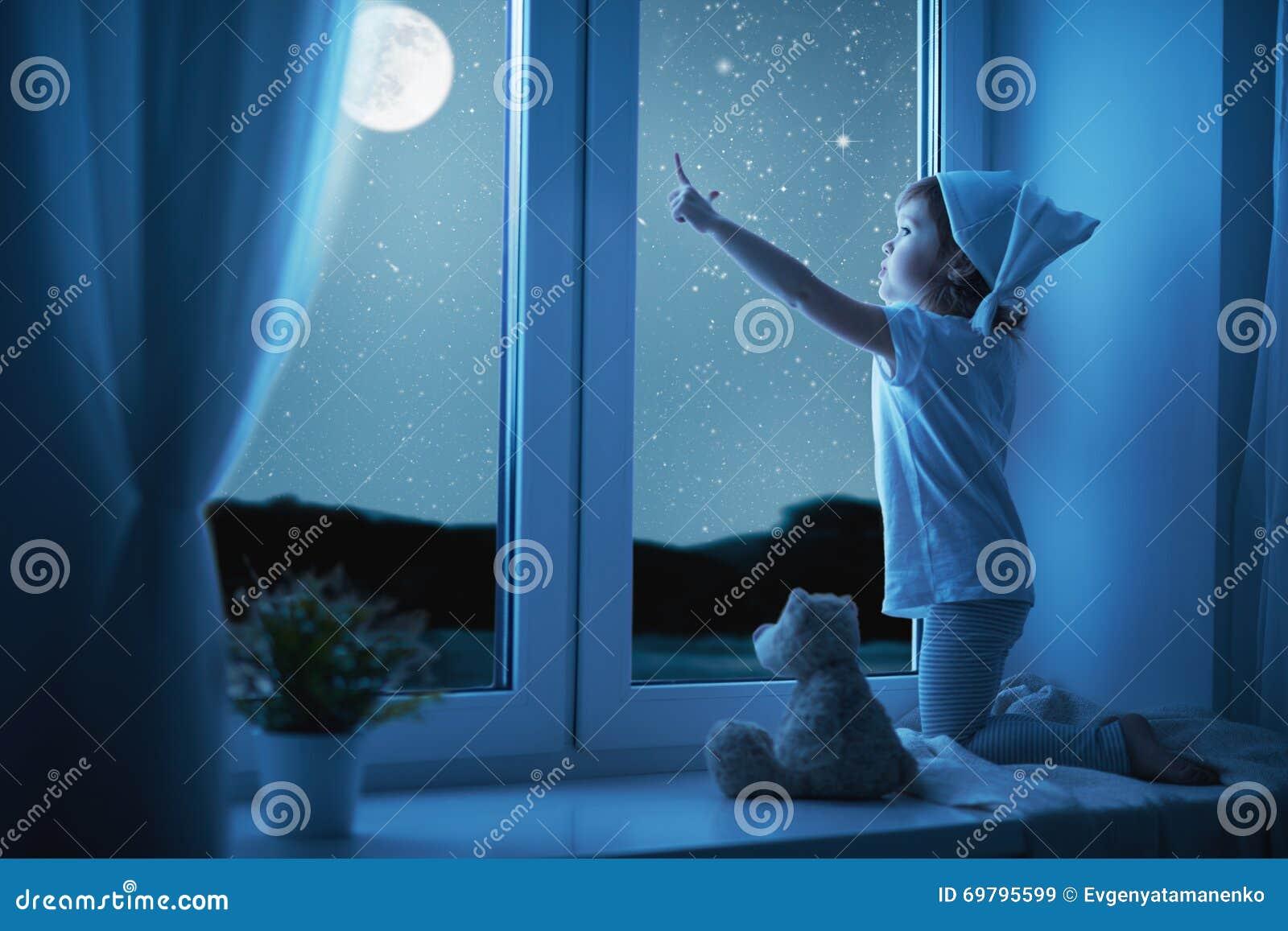 Barnliten flicka på fönstret som drömmer och beundrar stjärnklar himmel på
