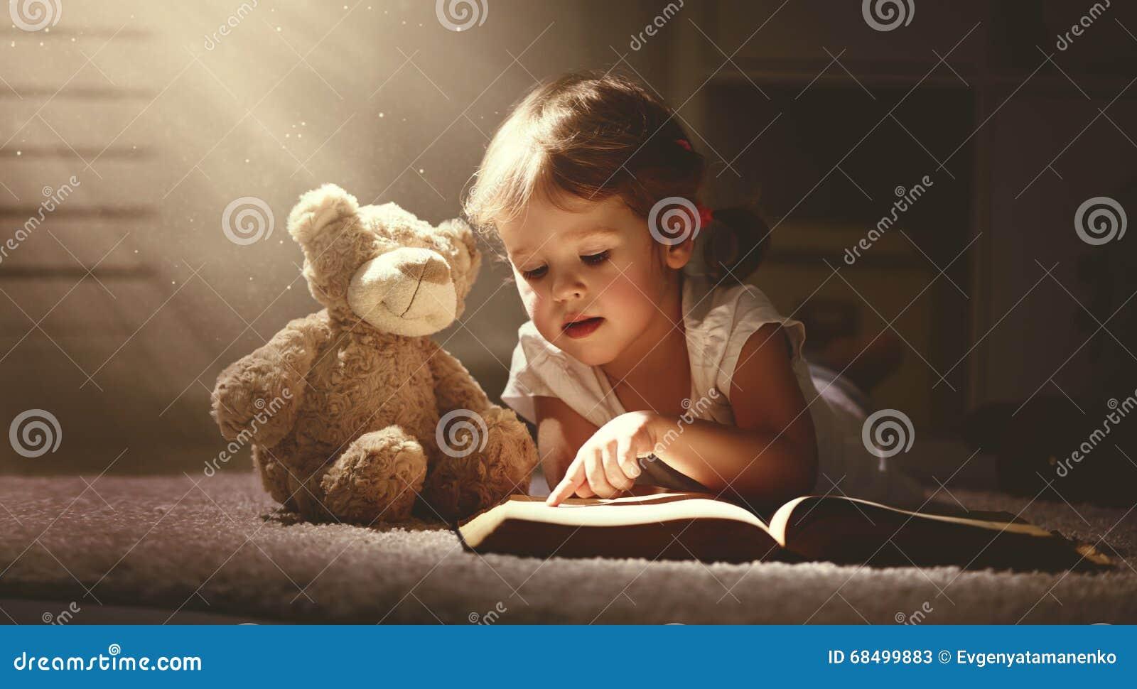 Barnliten flicka som läser en magisk bok i mörkerhem