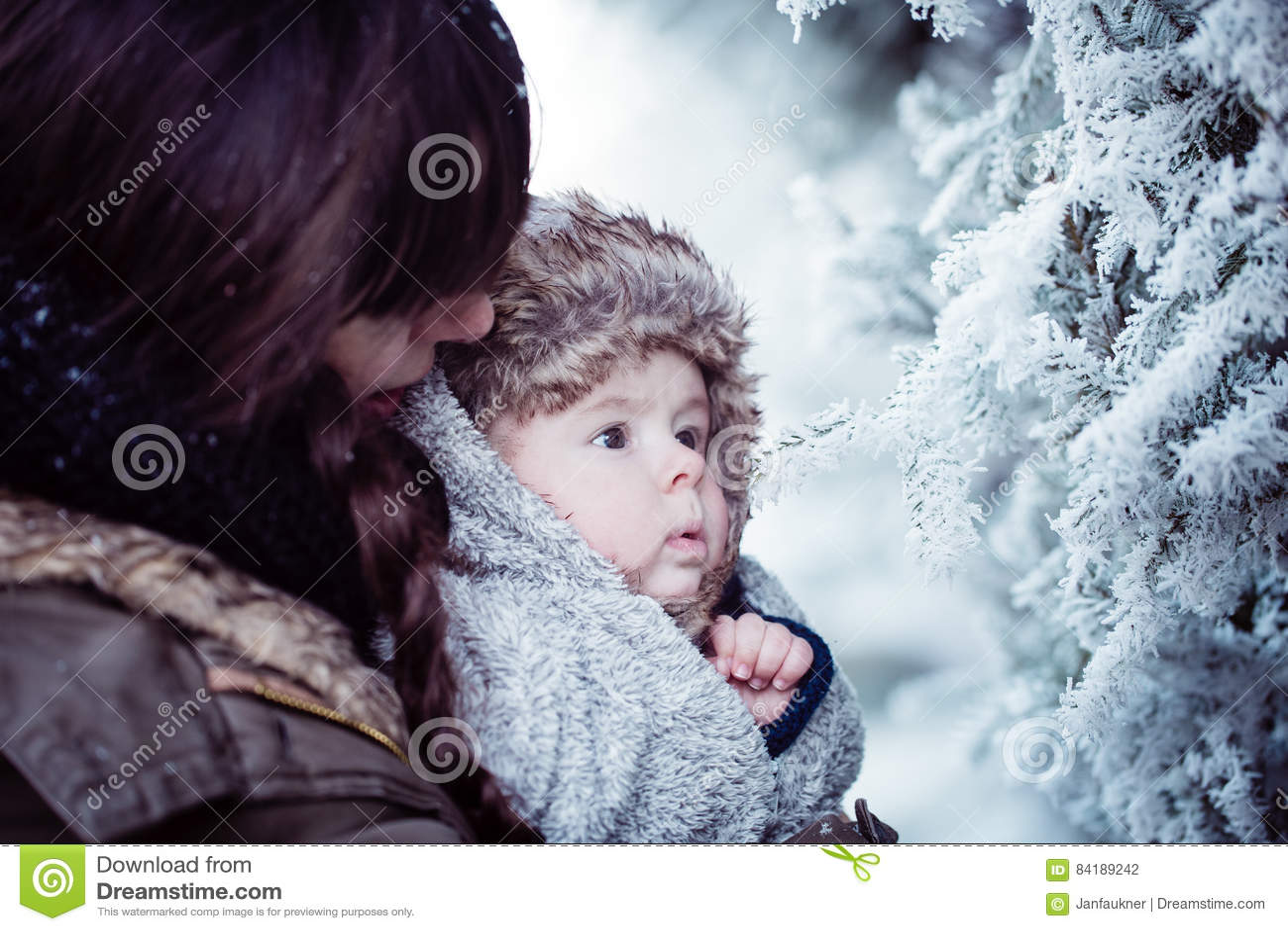 Barnmodern som rymmer hennes nyfött, behandla som ett barn i vinter