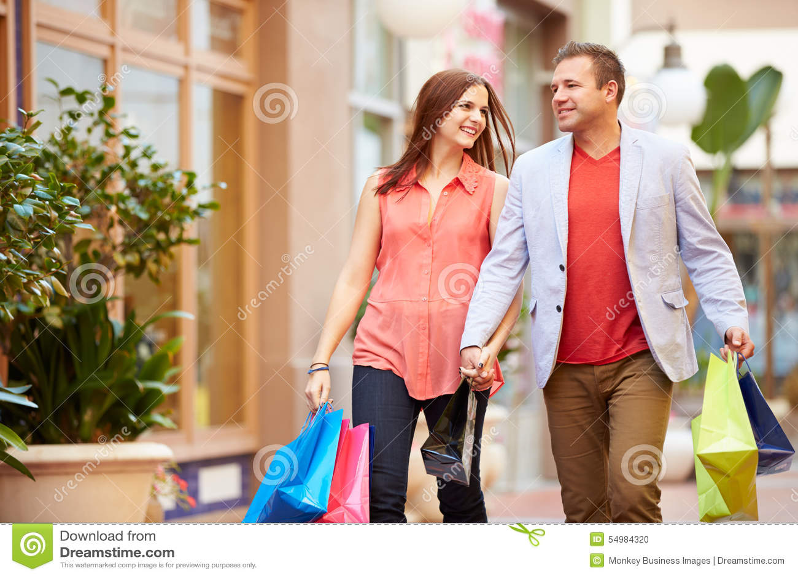 Barnpar som går till och med galleria med shoppingpåsar