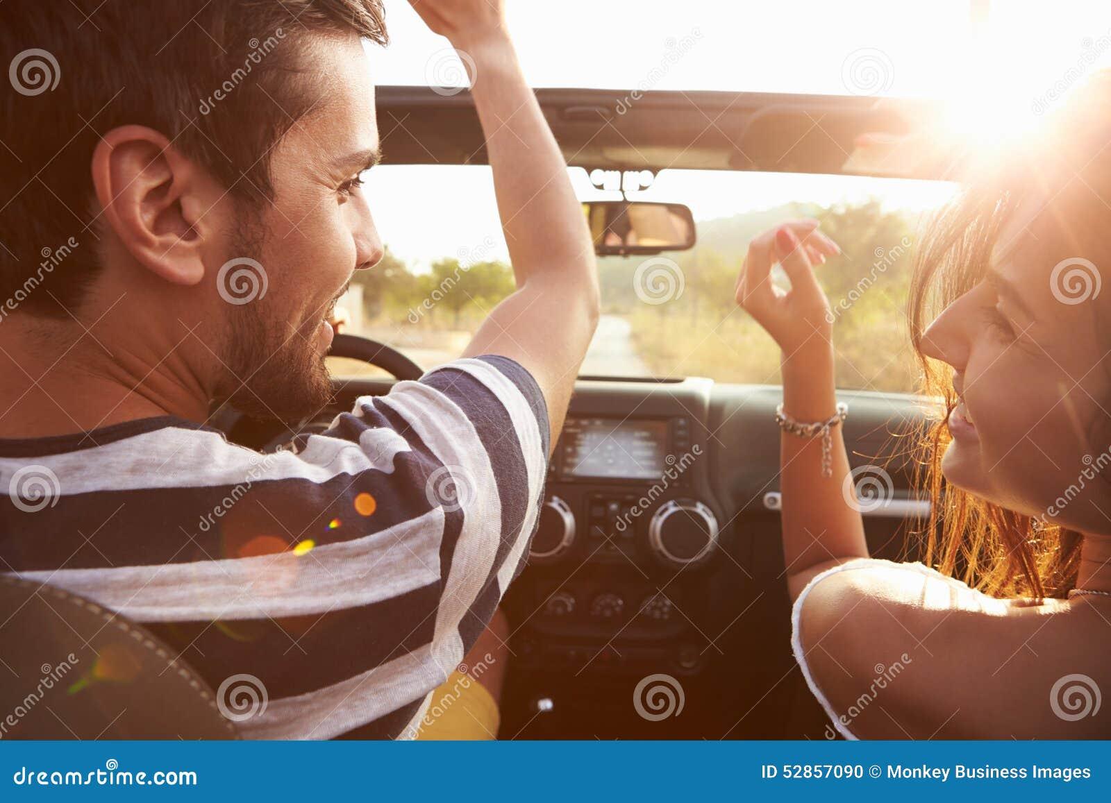 Barnpar som kör längs landsvägen i öppen bästa bil