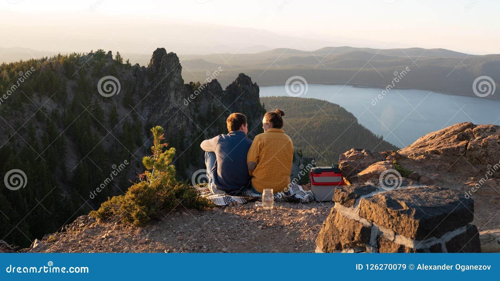 Barnpar som tycker om solnedgång över berg