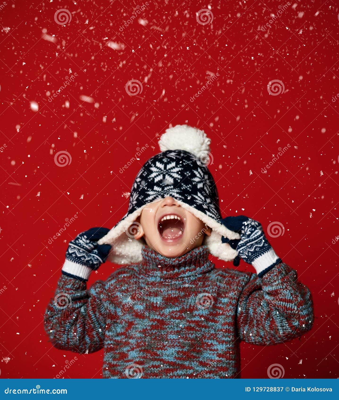 Barnpojke i stucken hatt och tröja och tumvanten som har gyckel över färgrik röd bakgrund
