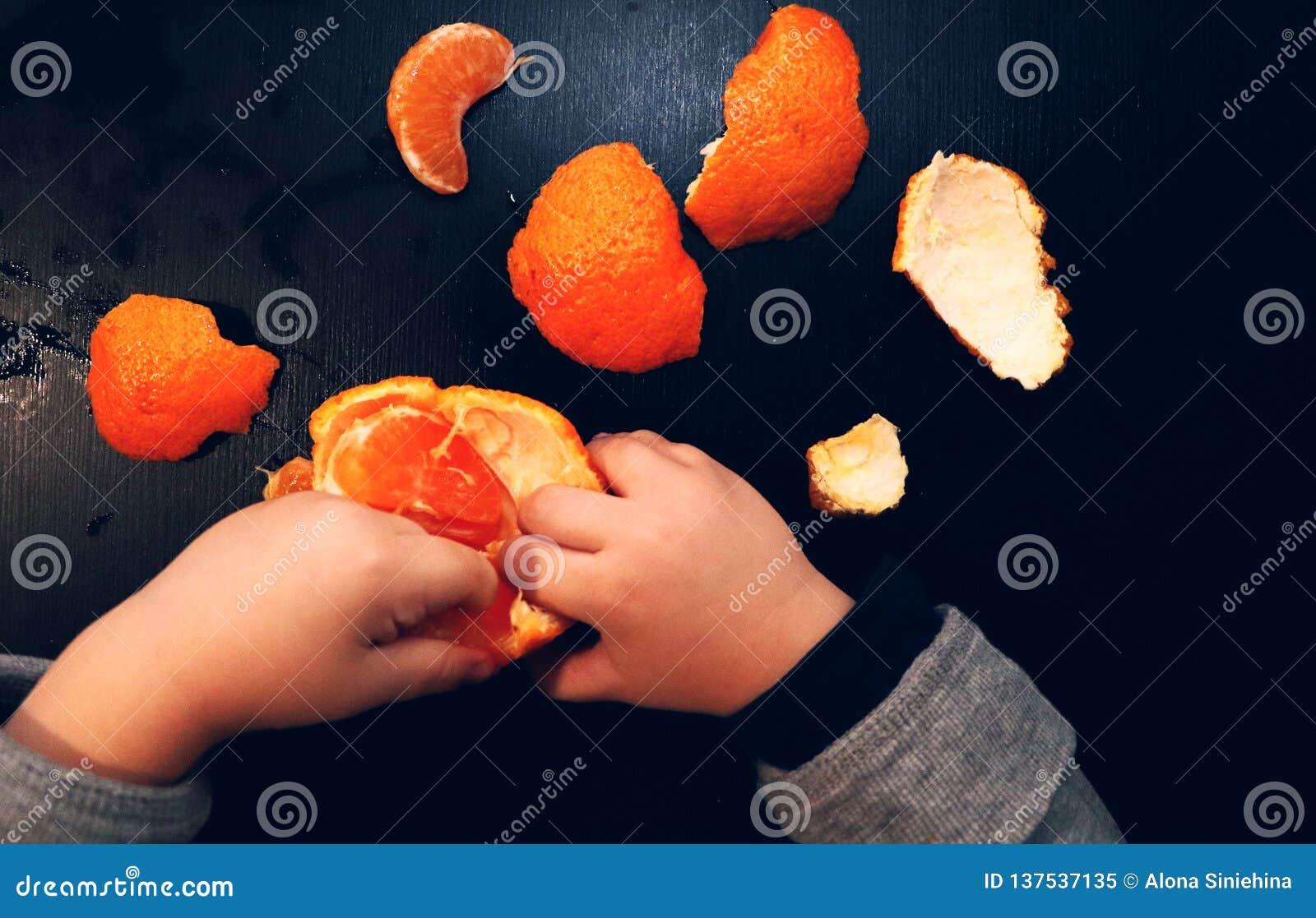 Barns händer borstar mandarinen på en svart bakgrund Barnet når för en skiva av mandarinen