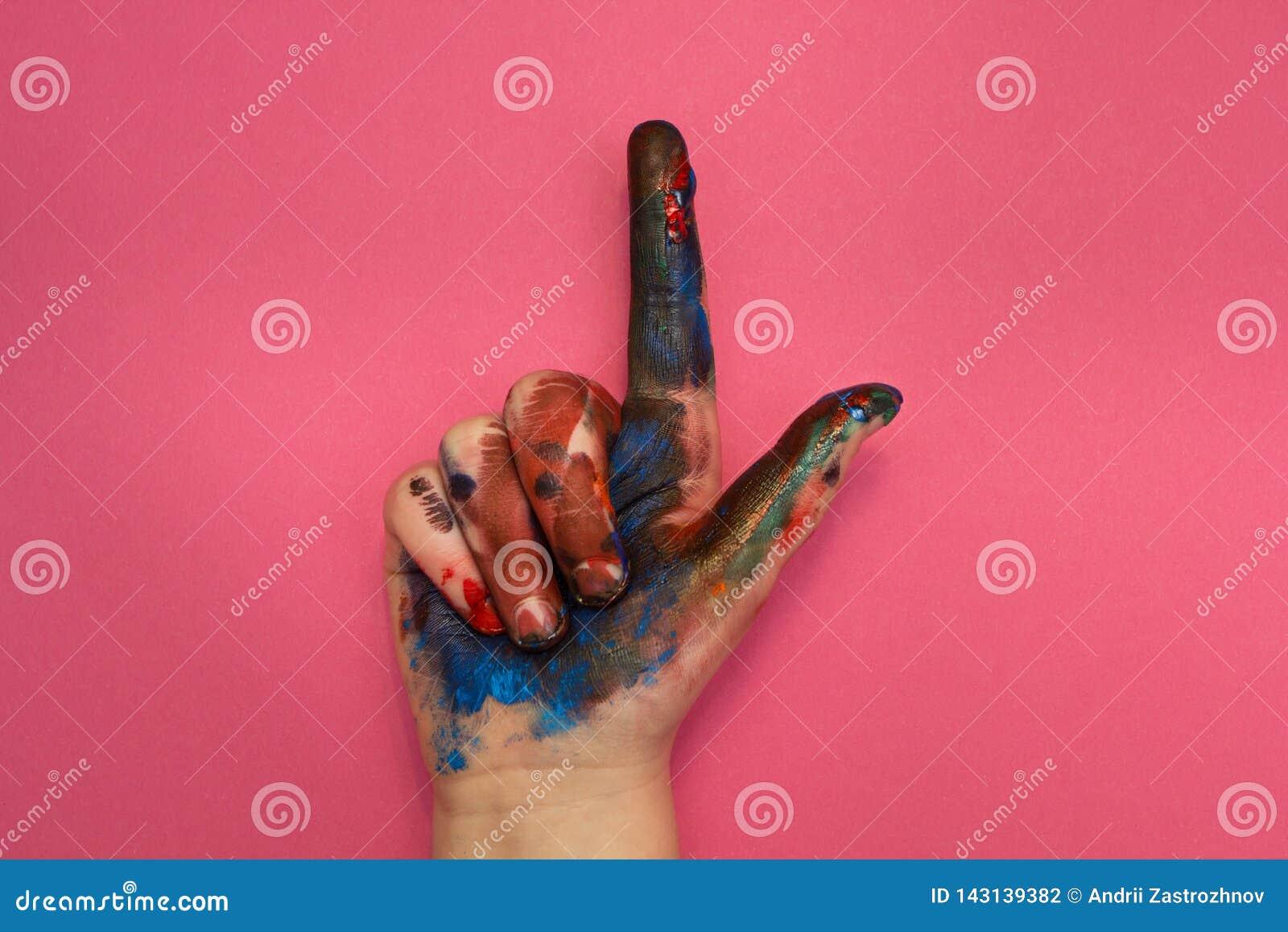 Barns hand i mångfärgade målarfärgpunkter upp på en rosa bakgrund
