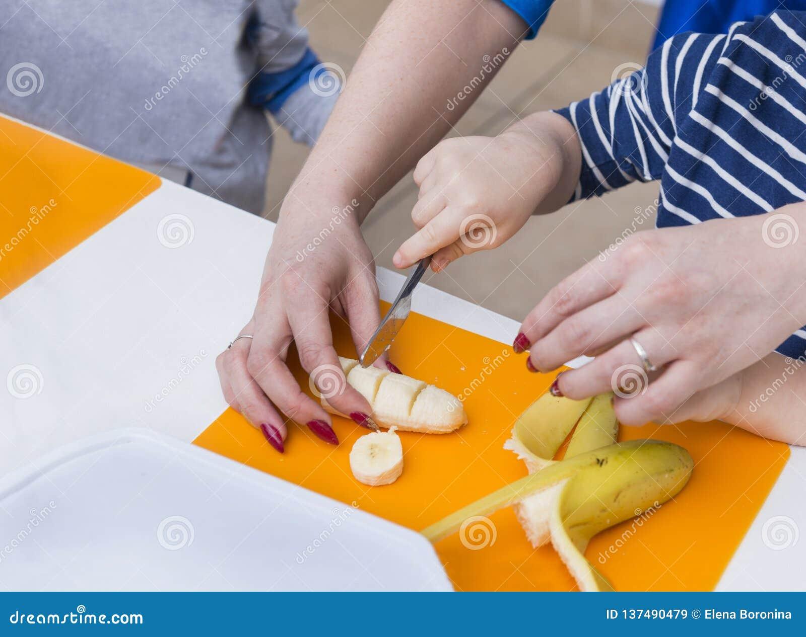 Barns hand med snitt för en kniv en banan, kvinnors händer