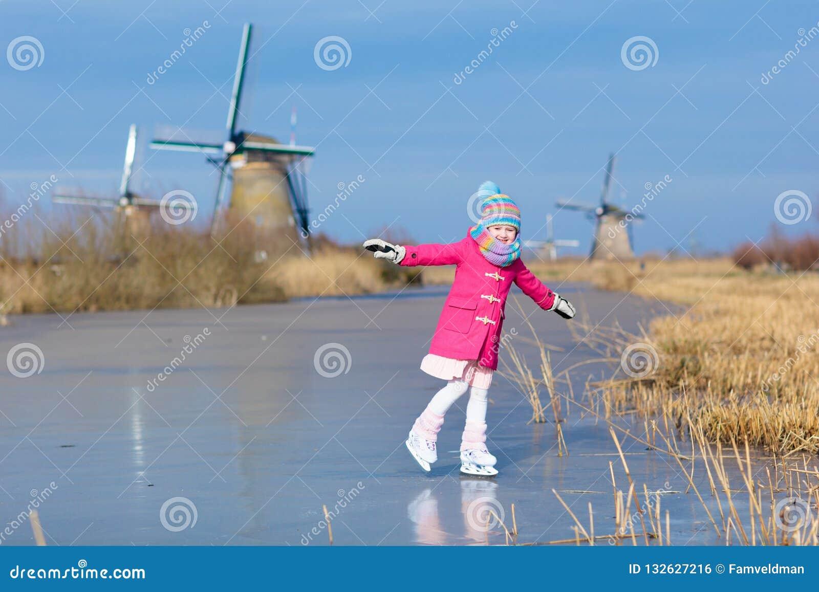 Barnskridskoåkningen på fryst maler kanalen i Holland