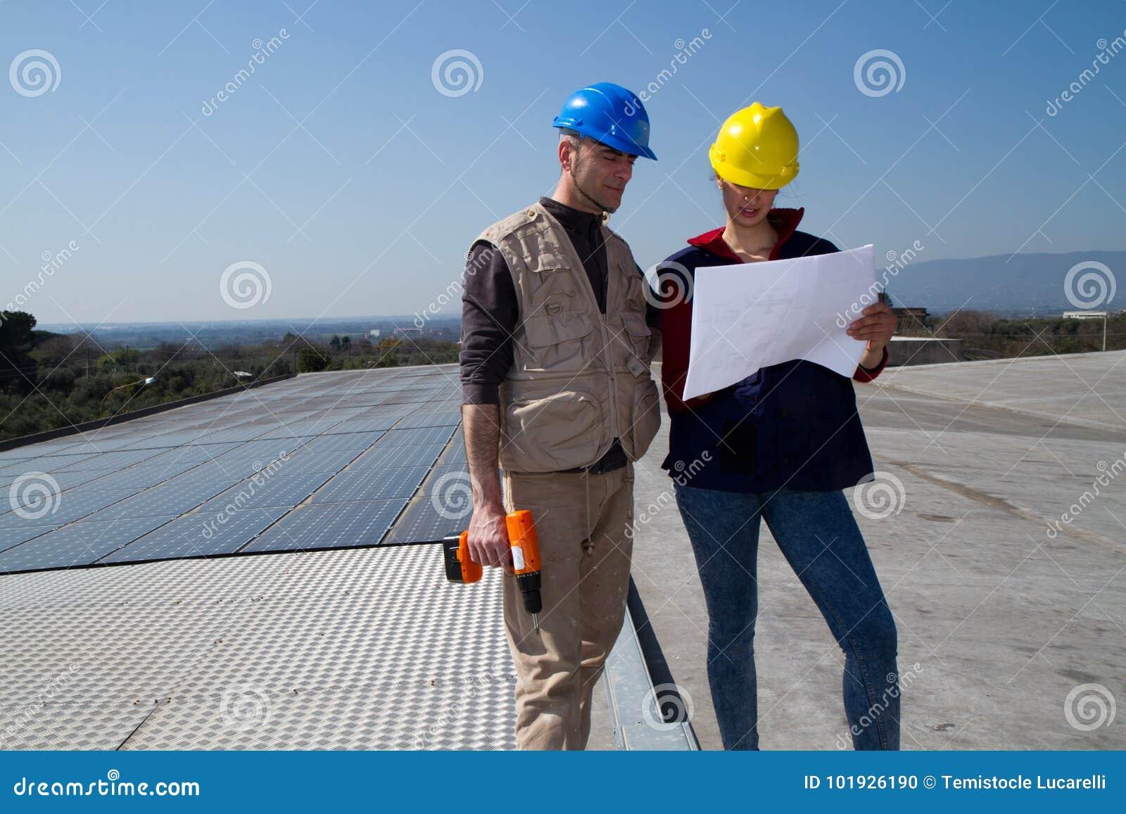 Barnteknikerflicka och kompetent arbetare på ett tak