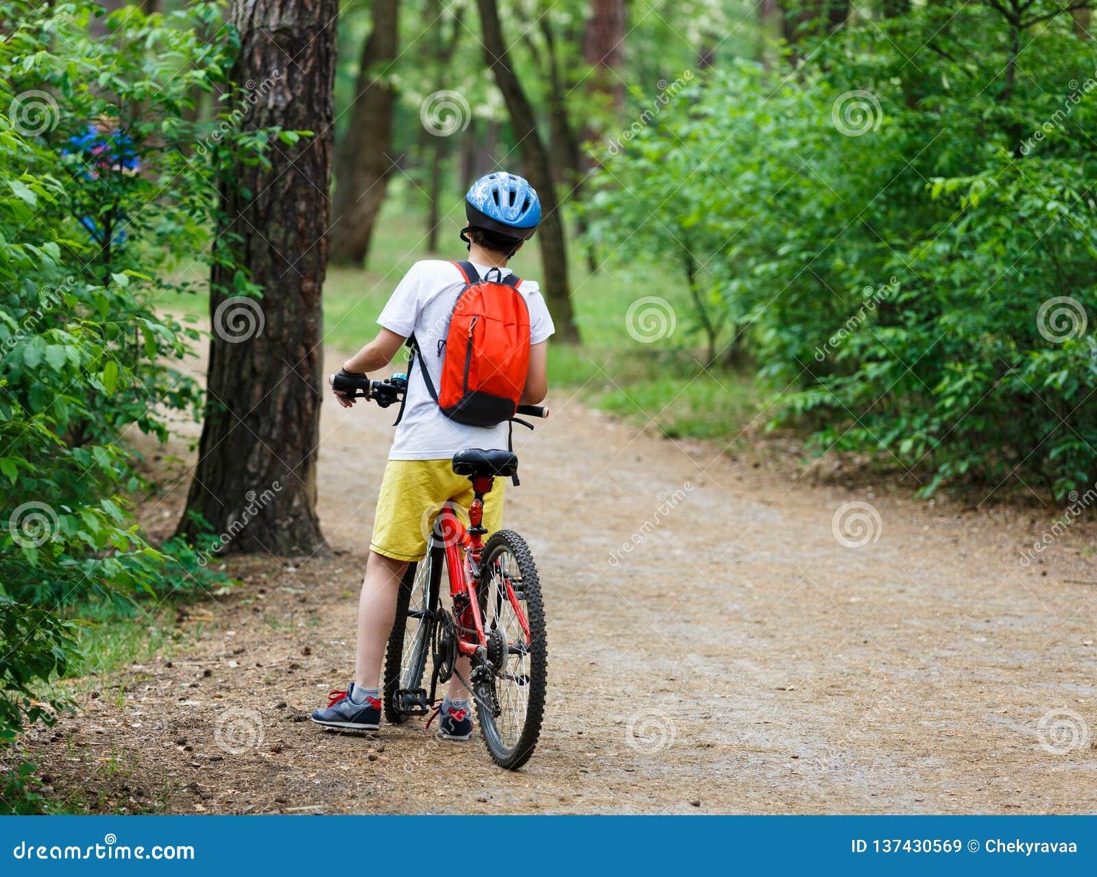 Barntonåring på cykelritt i skog på våren eller sommar Lycklig le pojke som utomhus cyklar i blå hjälm aktiv livsstil