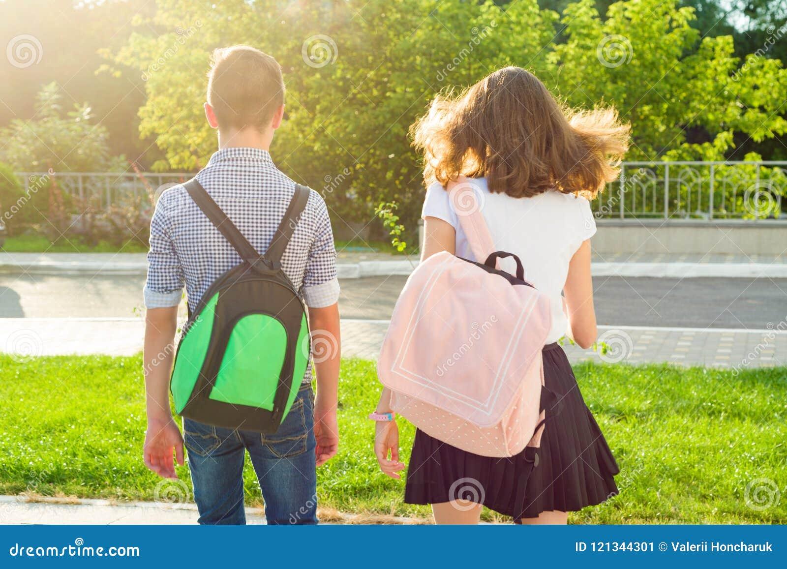 Barntonåringar går till skolan, baksidasikt Utomhus tonår med ryggsäckar