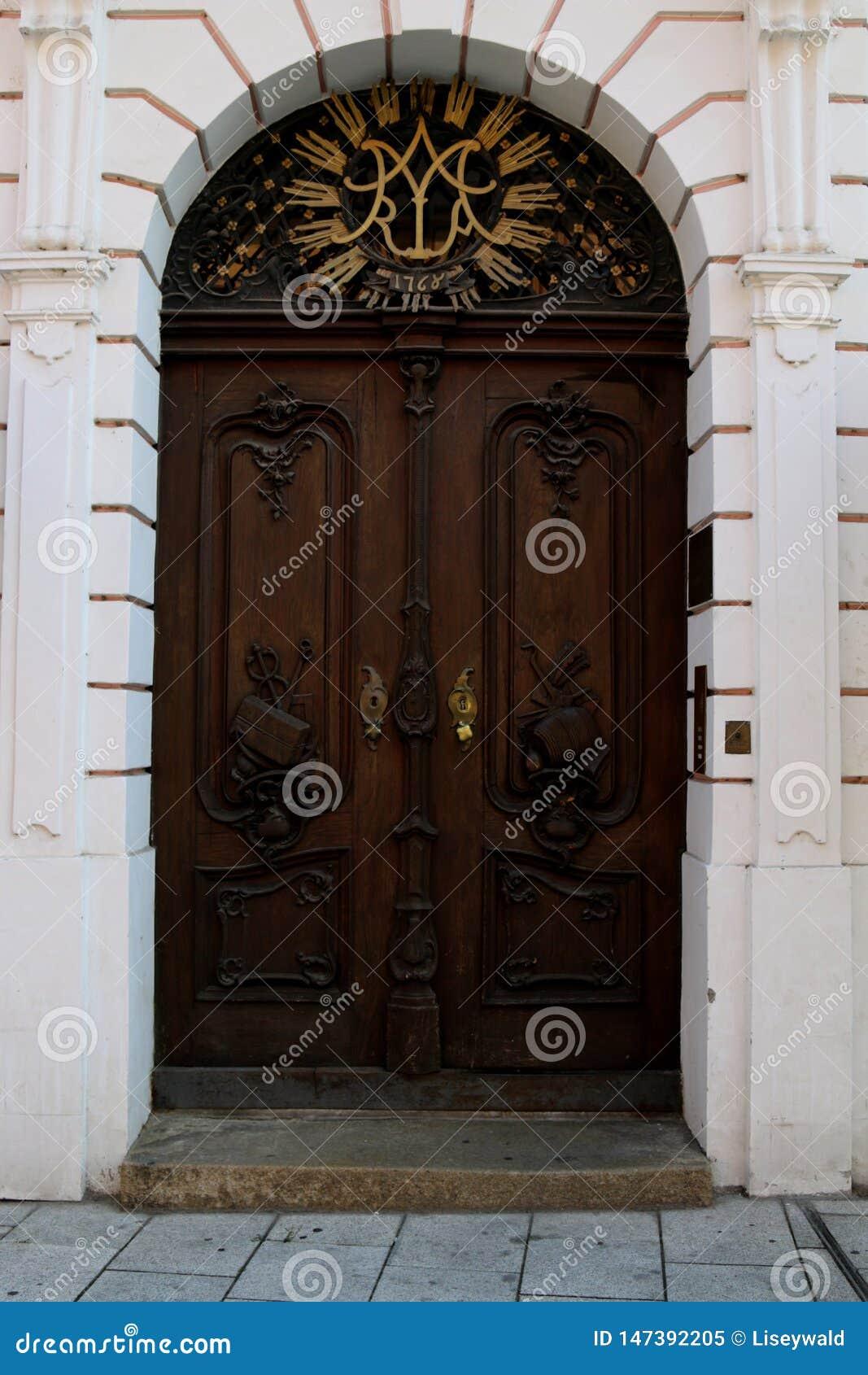 Barokke bruine deur met gouden en zwarte metaalelementen in een roze voorgevel