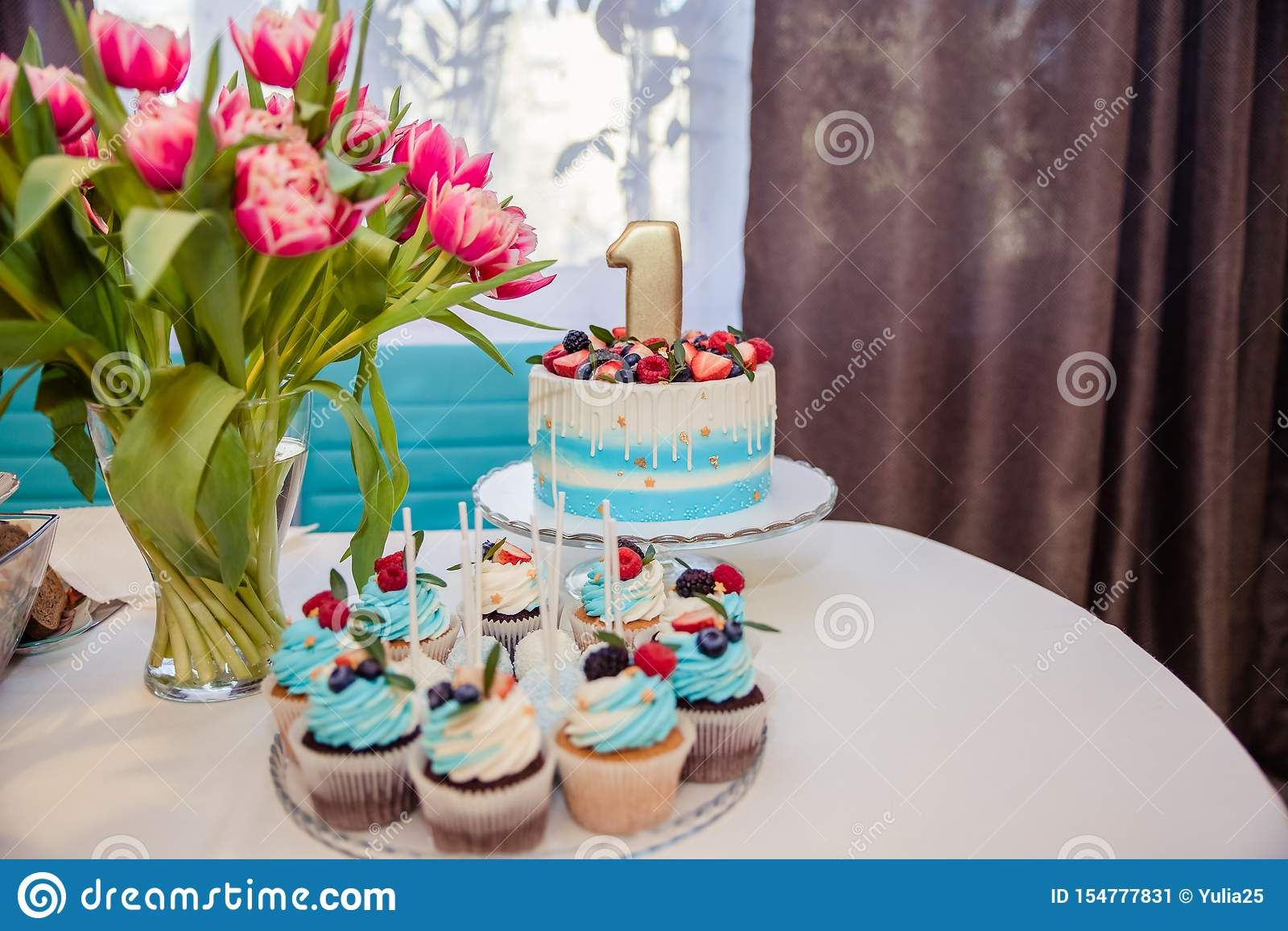 Barra de caramelo adornada con los dulces, las magdalenas y la torta para la 1ra fiesta de cumpleaños Decoraci?n interior para un