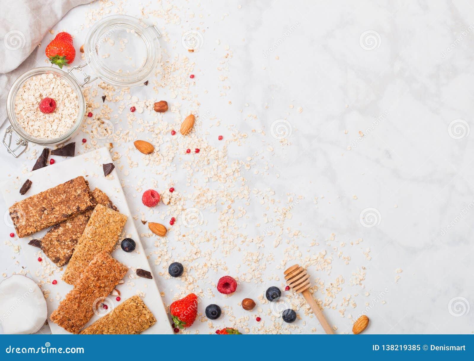 Barra de granola orgánica del cereal con las bayas en el tablero de mármol con la cuchara de la miel y el tarro de la avena y de