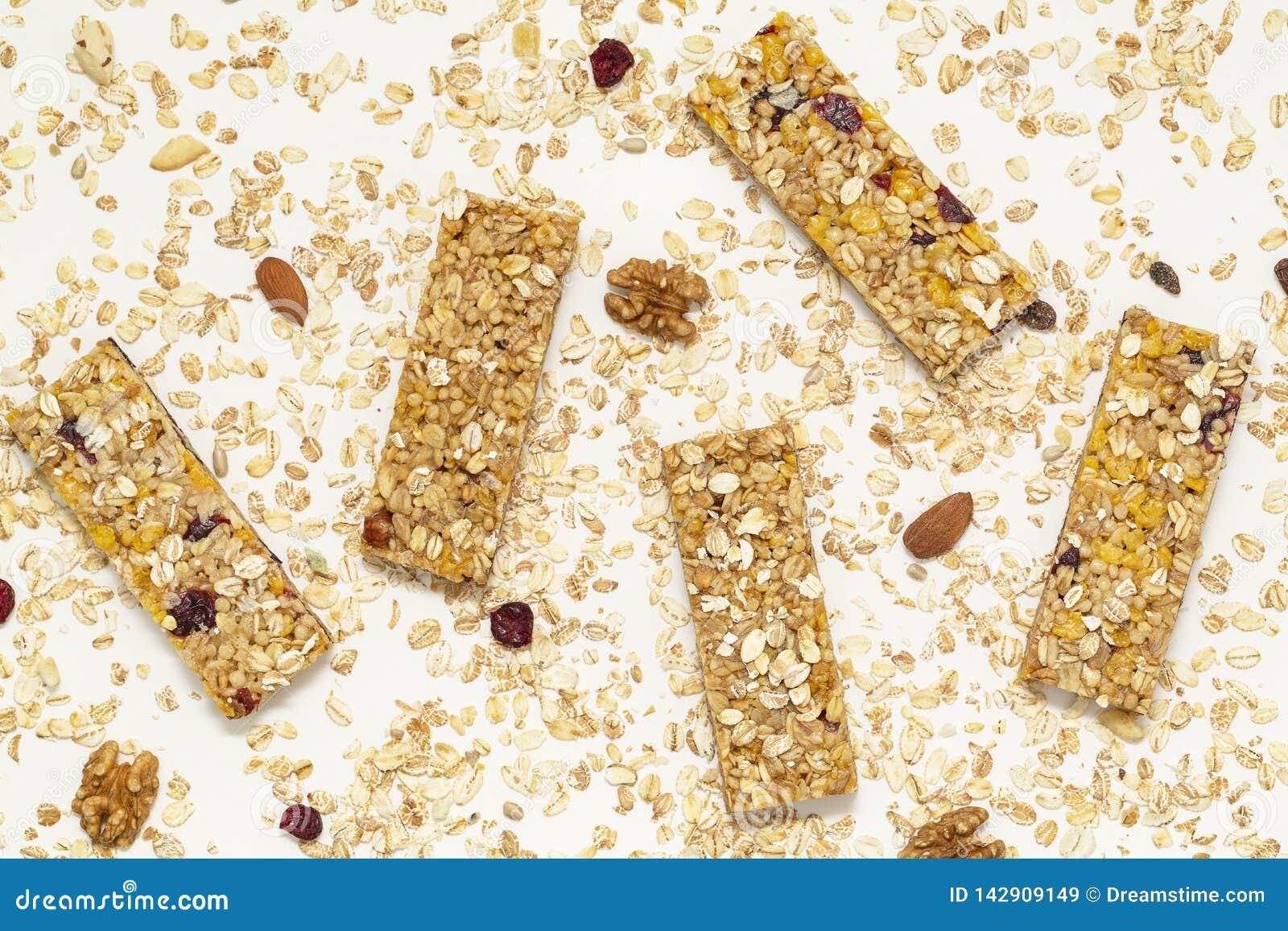 Barra de Granola Petisco doce saud?vel da sobremesa Barra de granola do cereal com porcas, fruto e bagas em uma tabela branca