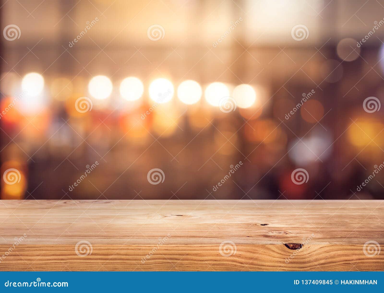 Barra de madeira do tampo da mesa com bokeh claro colorido do borrão no café, fundo do restaurante