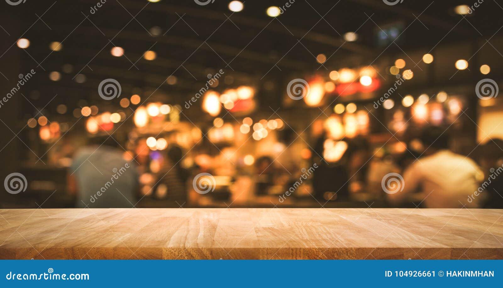 Barra de madeira do tampo da mesa com bokeh da luz do borrão no café escuro da noite