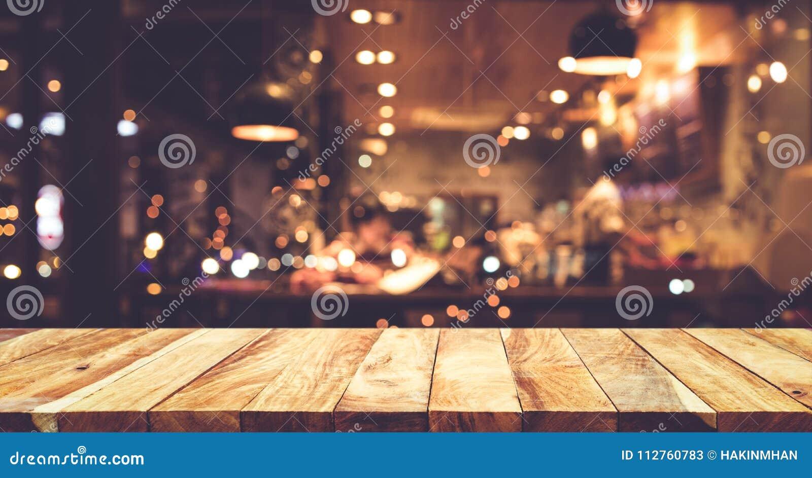 Barra de madeira do tampo da mesa com fundo do café da noite do borrão